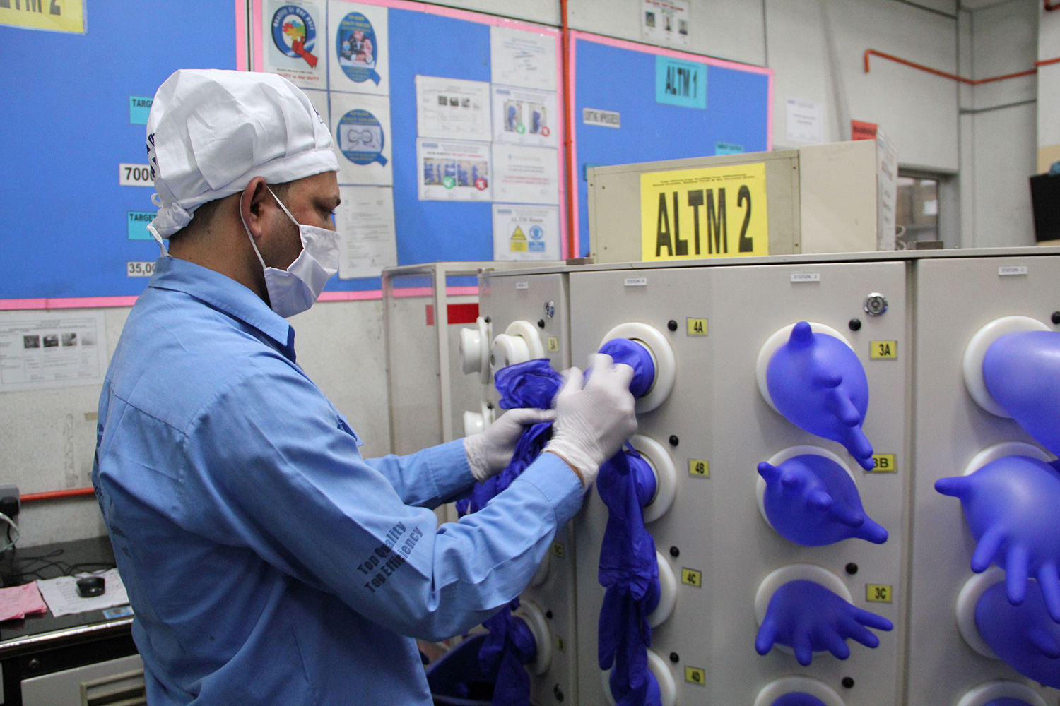 Picture shows the worker stretching gloves over nozzles that inflate them.