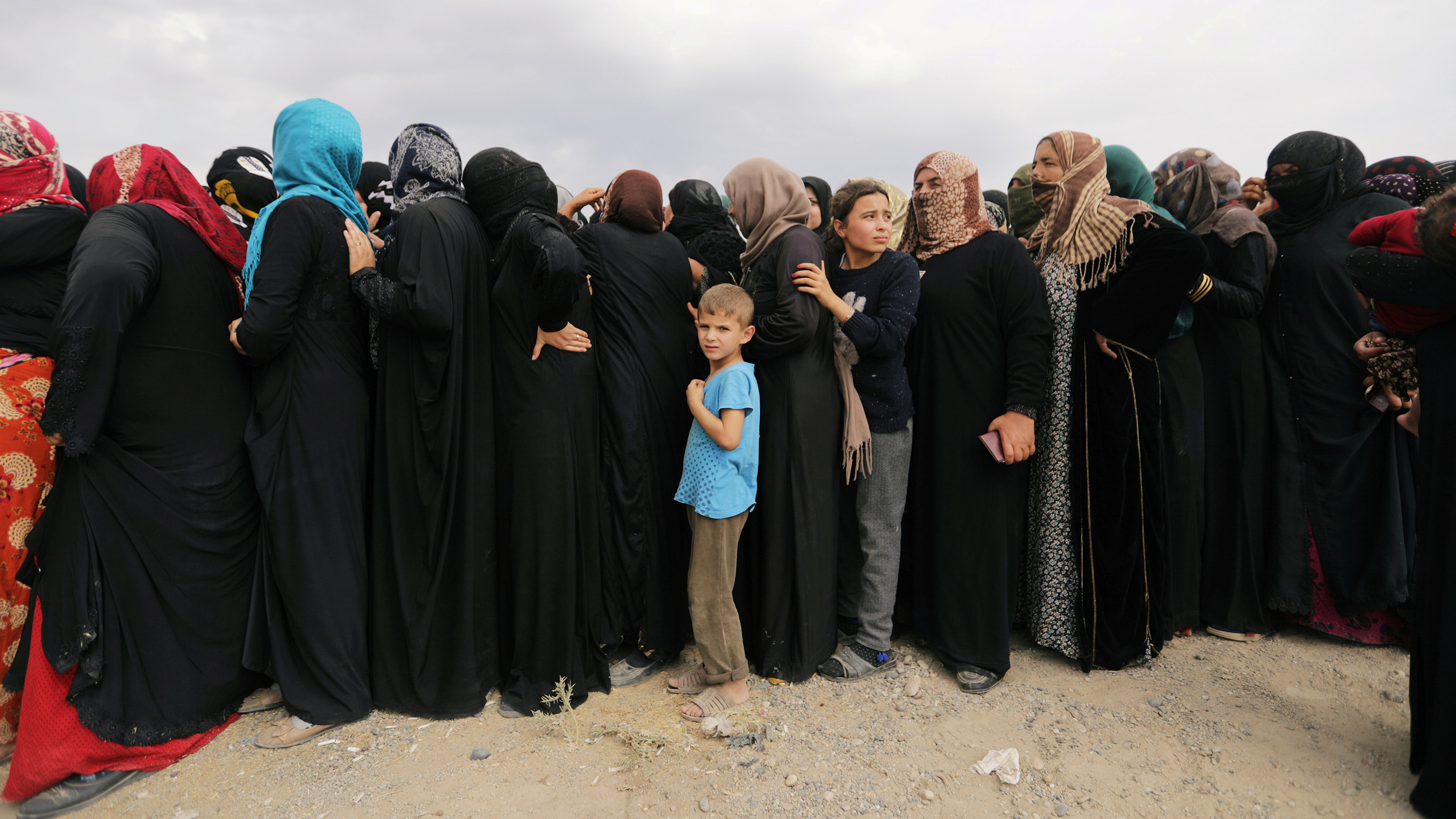 The photo shows a line of mostly women, all in black coverings, with a single boy in a light blue shirt in line with them. It is striking because his shirt stands out against a sea of black.