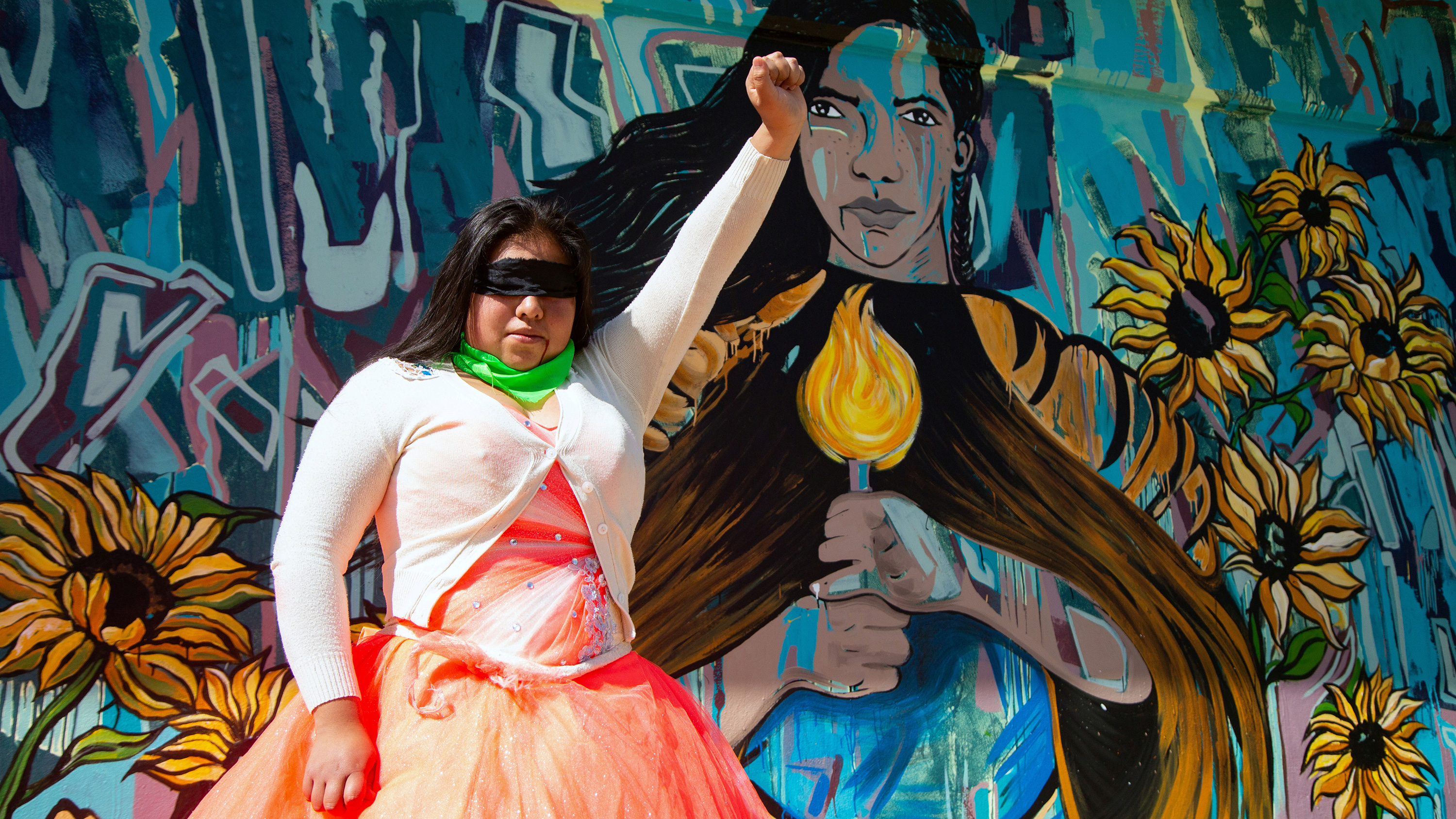 The photo shows a woman in an orange dress and white cardigan with a blindfold over her face holding her fist in the air while she stands in front of a painted mural of a woman holding a candle.