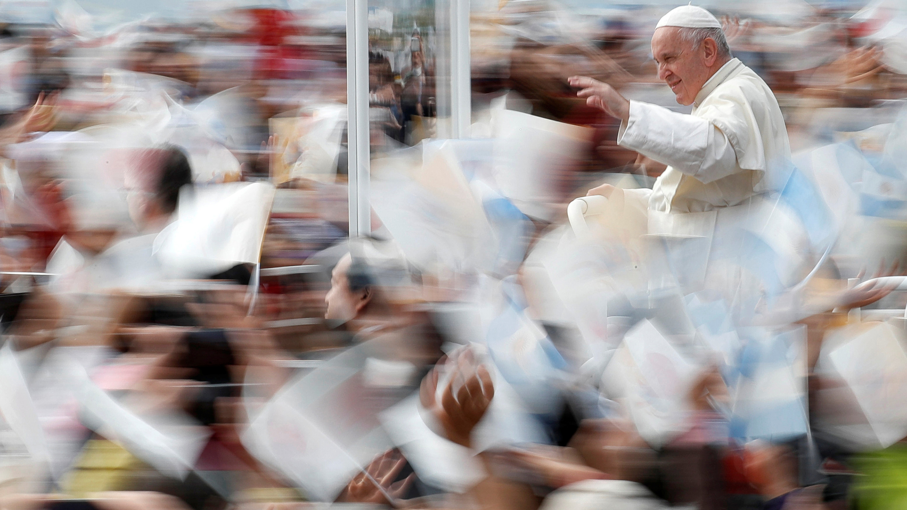 The photo shows the pope in clear focus while all the bustling crowds around him are moving and out of focus.