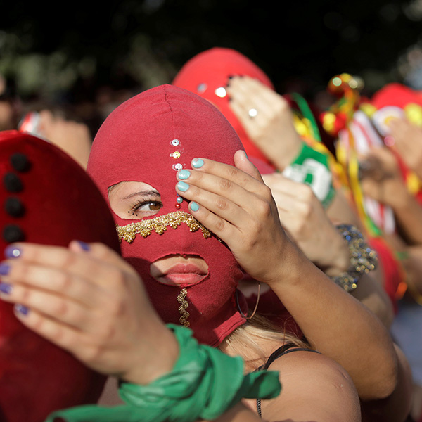 """We cannot afford to unsee domestic abuse after COVID-19,"" the authors write. Here women wearing masks take part in a protest against gender violence in Santiago, Chile, on December 6, 2019. The photo is a striking image of women wearing red masks lined up, each person holding a hand over one eye of the person in front of them. REUTERS/Andres Martinez Casares"