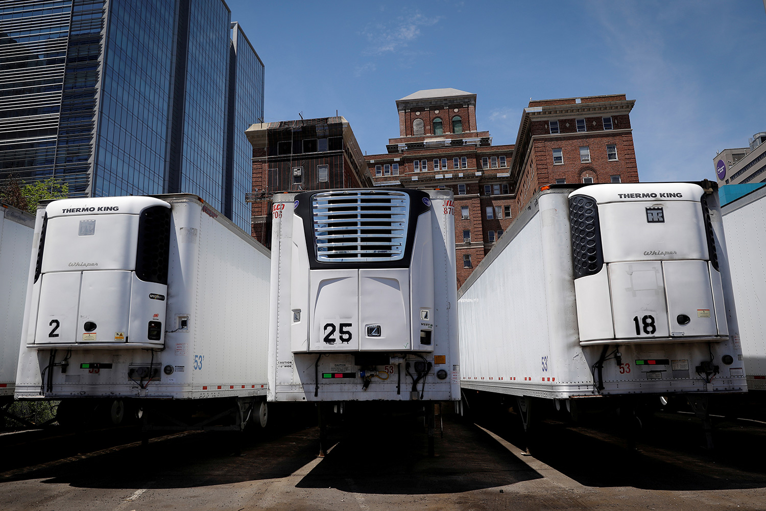 Image shows a row of huge refrigerated trucks parked together amid buildings under a clear blue sky.