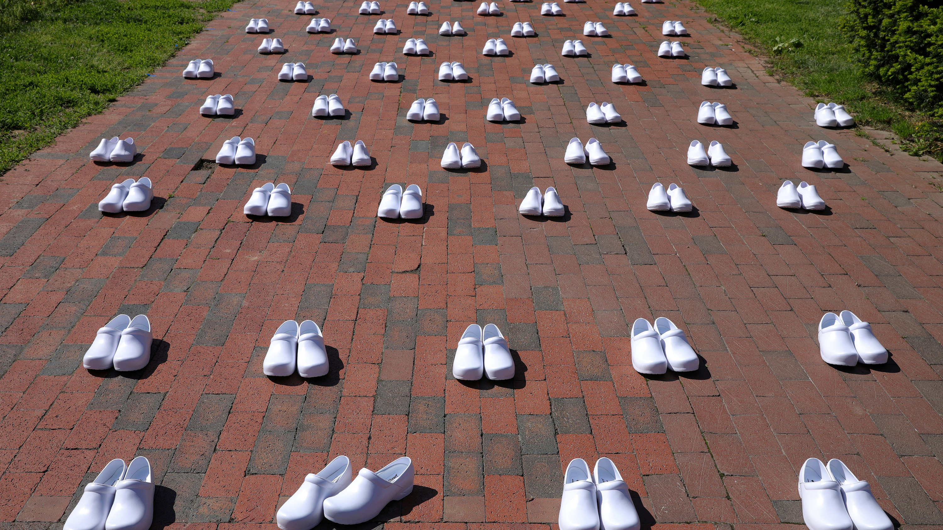 The photo shows an array of white shoes lined up along a paved path. One pair in the front is slightly askew.