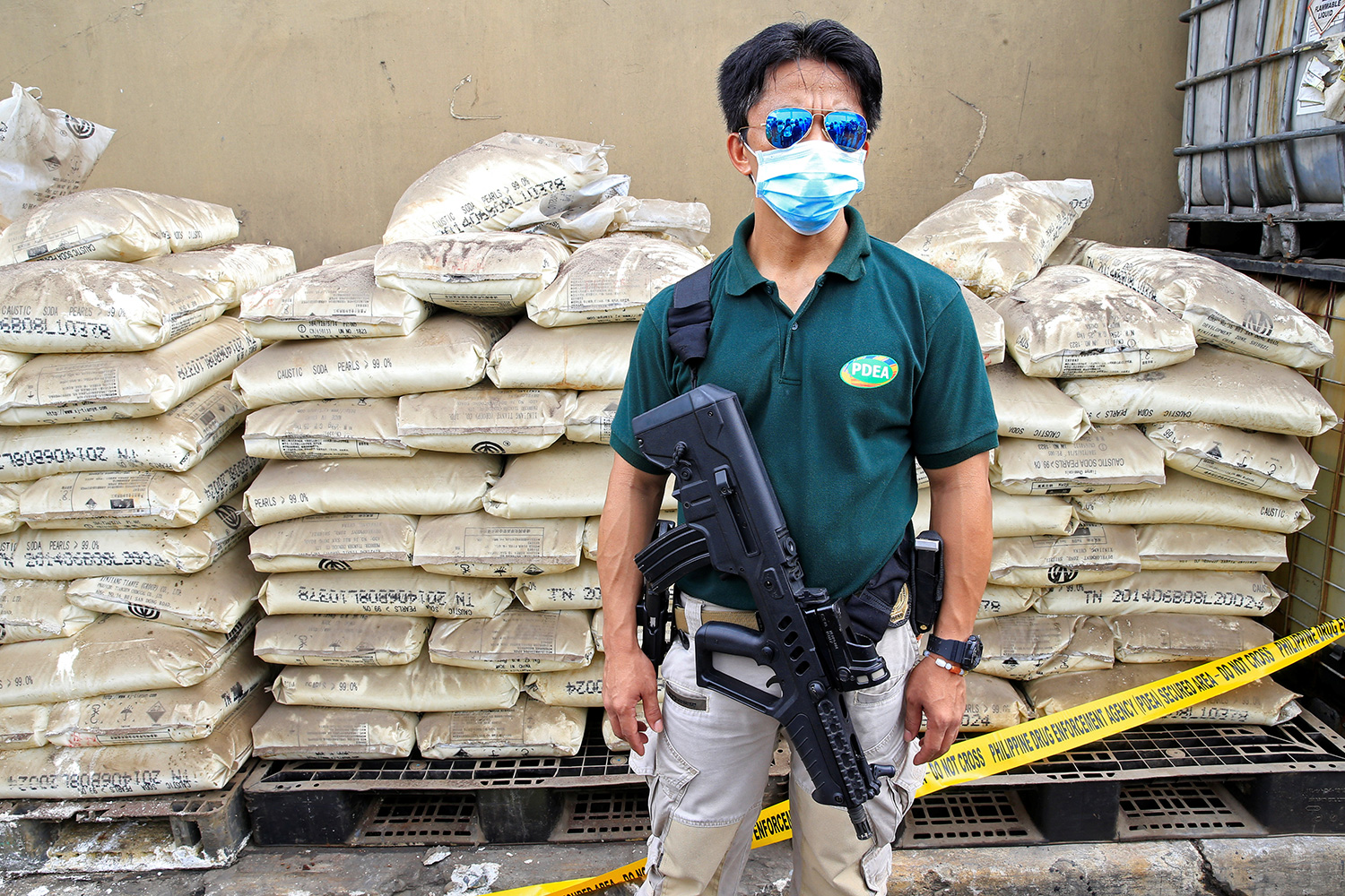 The photo shows the agent in reflective glasses standing in front of a huge stack of bagged chemicals.