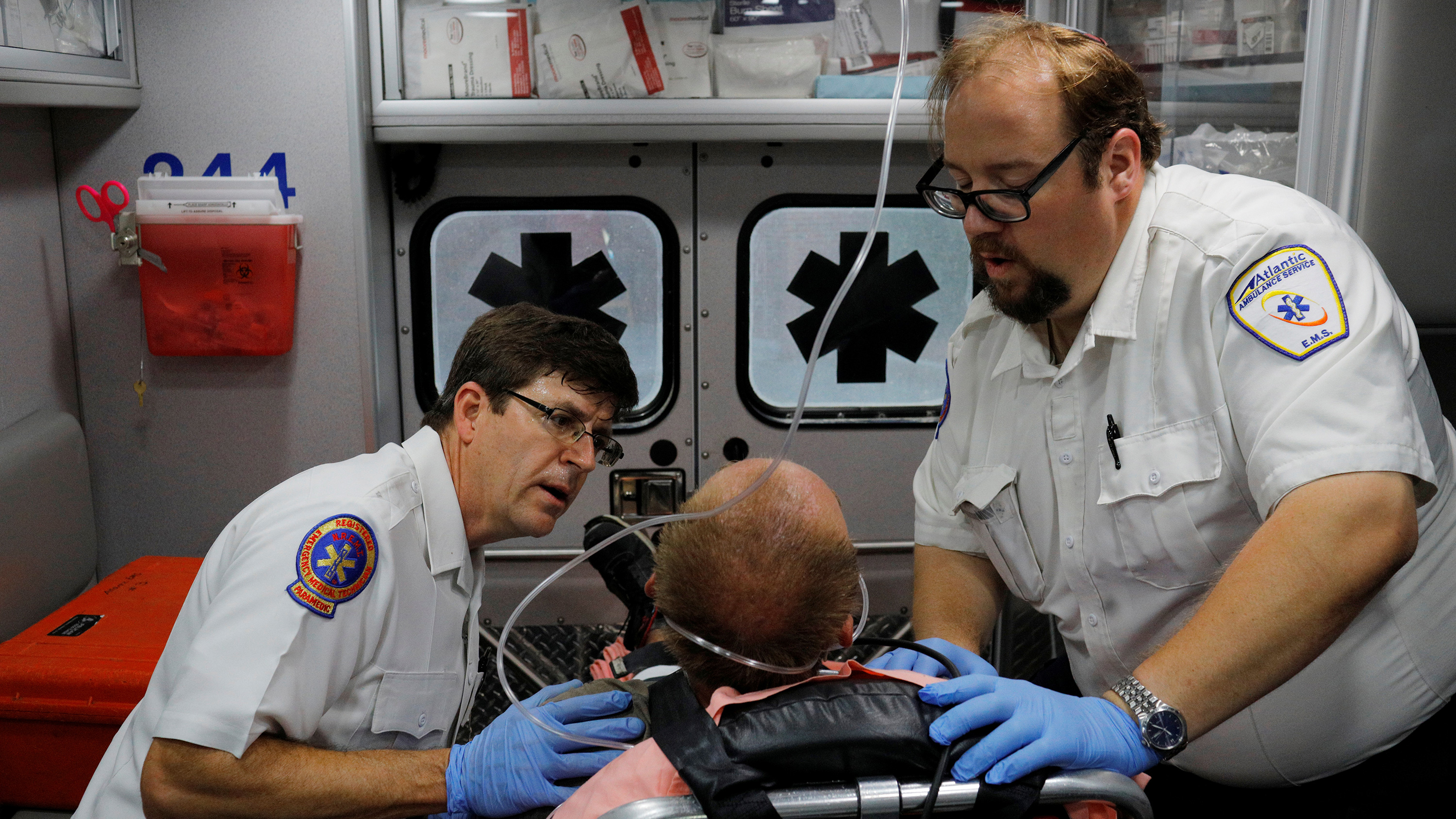 The photo shows the two medics administering to a man in a gurney.