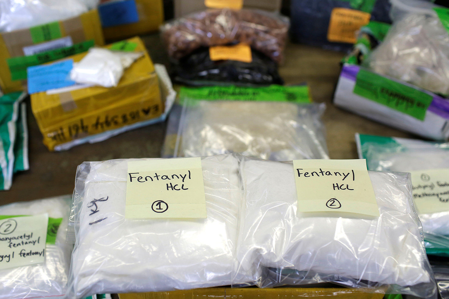 Picture shows several large clear plastic bags labeled fentanyl stacked on a table.
