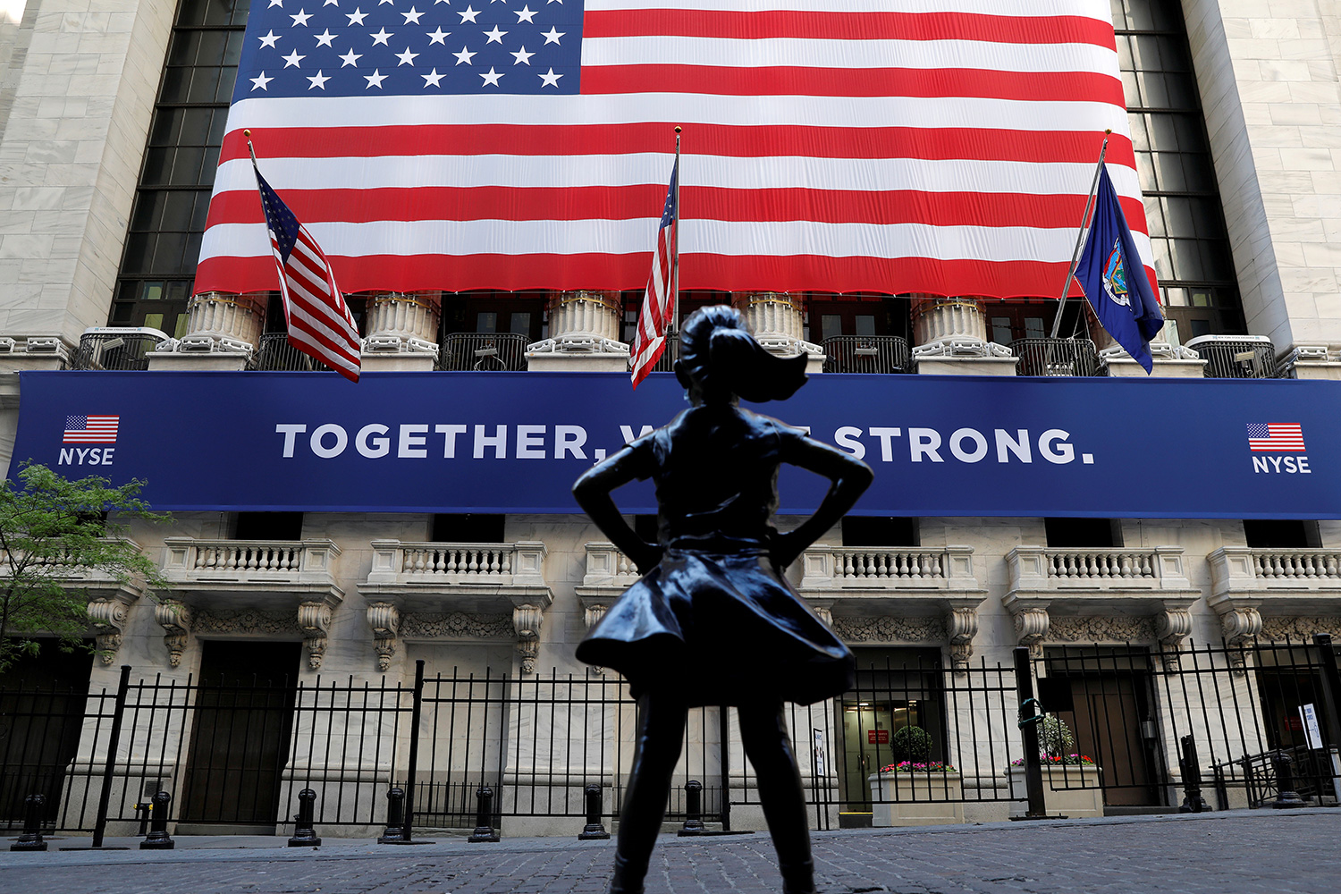 "The ""Fearless Girl"" statue is seen outside the New York Stock Exchange following first trading session since its March coronavirus lockdown in the Manhattan borough of New York City on May 26, 2020. The photo shows the statue with a huge American flag in the background. REUTERS/Mike Segar"