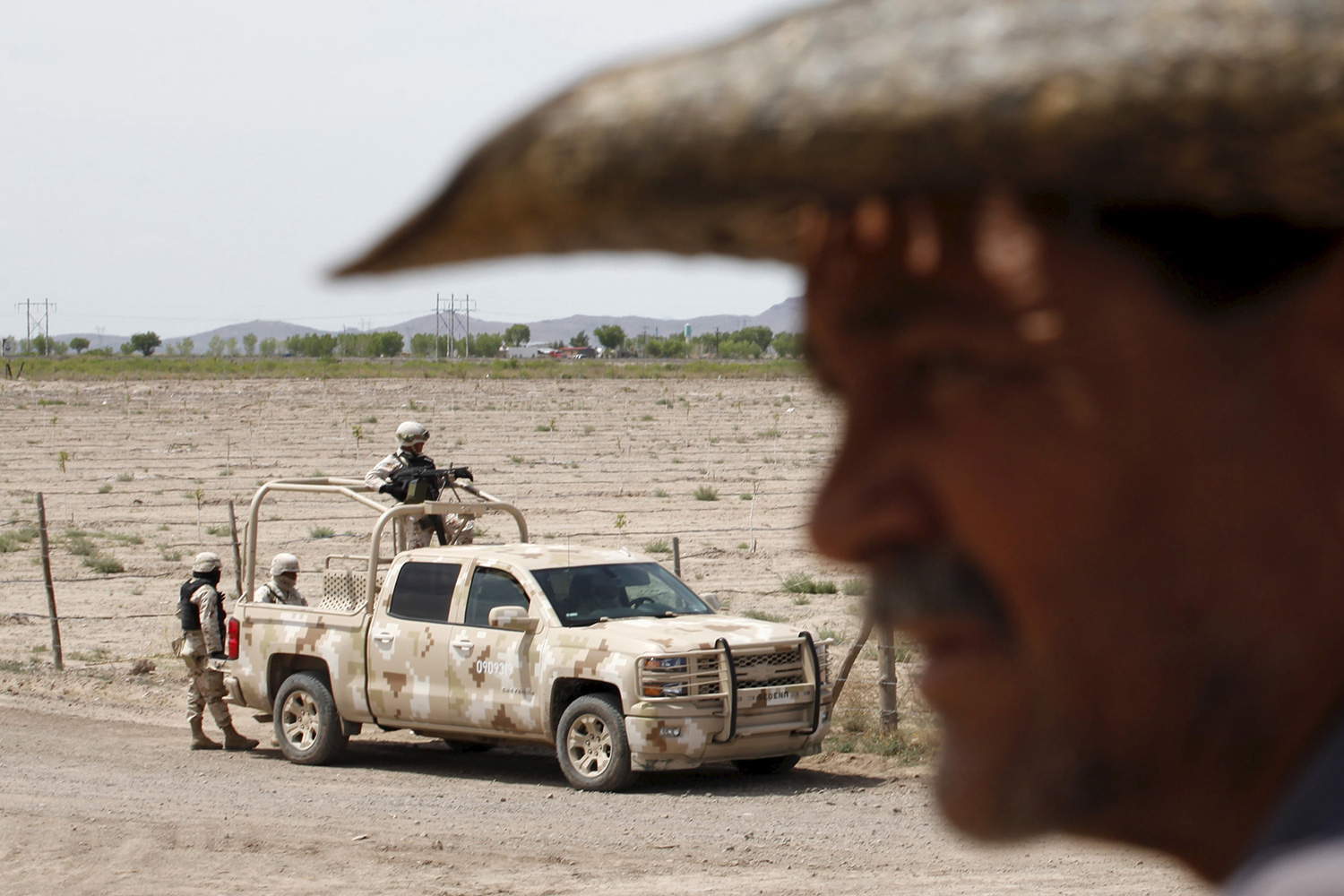 The photo shows a dusty dirt road with a truck of soldiers on it while a man stands out of focus in the foreground.