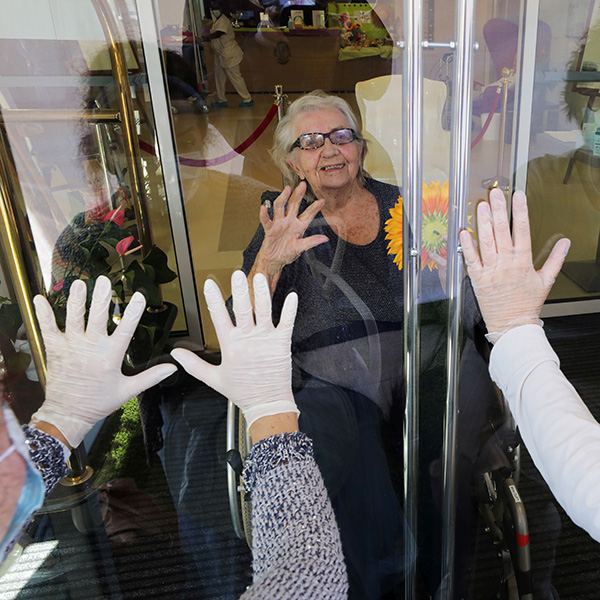 "A resident named Mrs. Oury reacts as her daughters wave behind a glass during a visit at ""Les Figuiers"" retirement home amid the coronavirus outbreak in Villeneuve-Loubet, France, on April 23, 2020. The photo shows a woman from behind glass while two others stand with their backs to the camera looking in. They all have their hands up. REUTERS/Eric Gaillard"