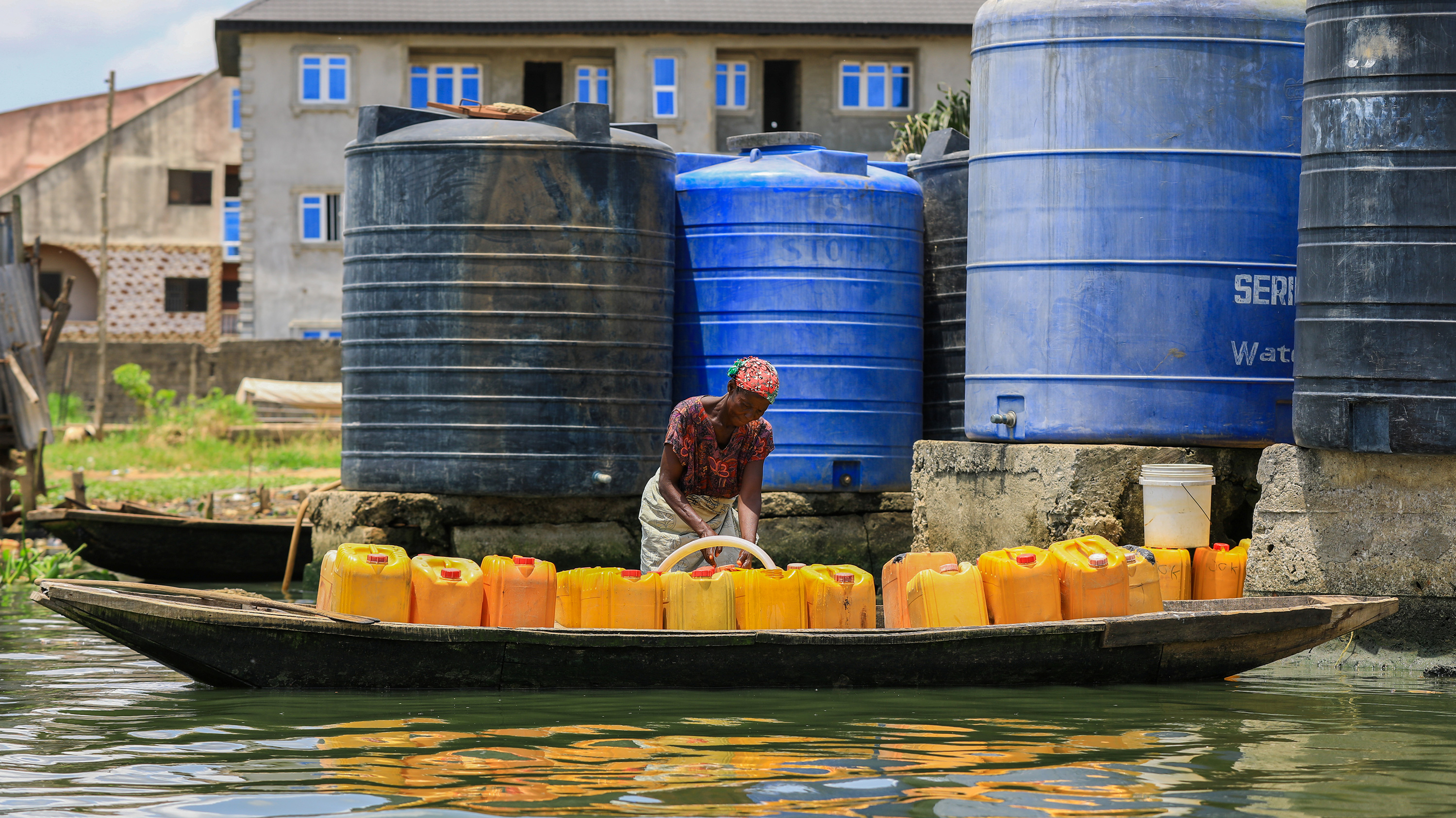 Picture shows a woman with a long dugout canoe pulled up to a filling station with a number of towering water tanks. She is filling a row of yellow jerrycans lined up inside the canoe.