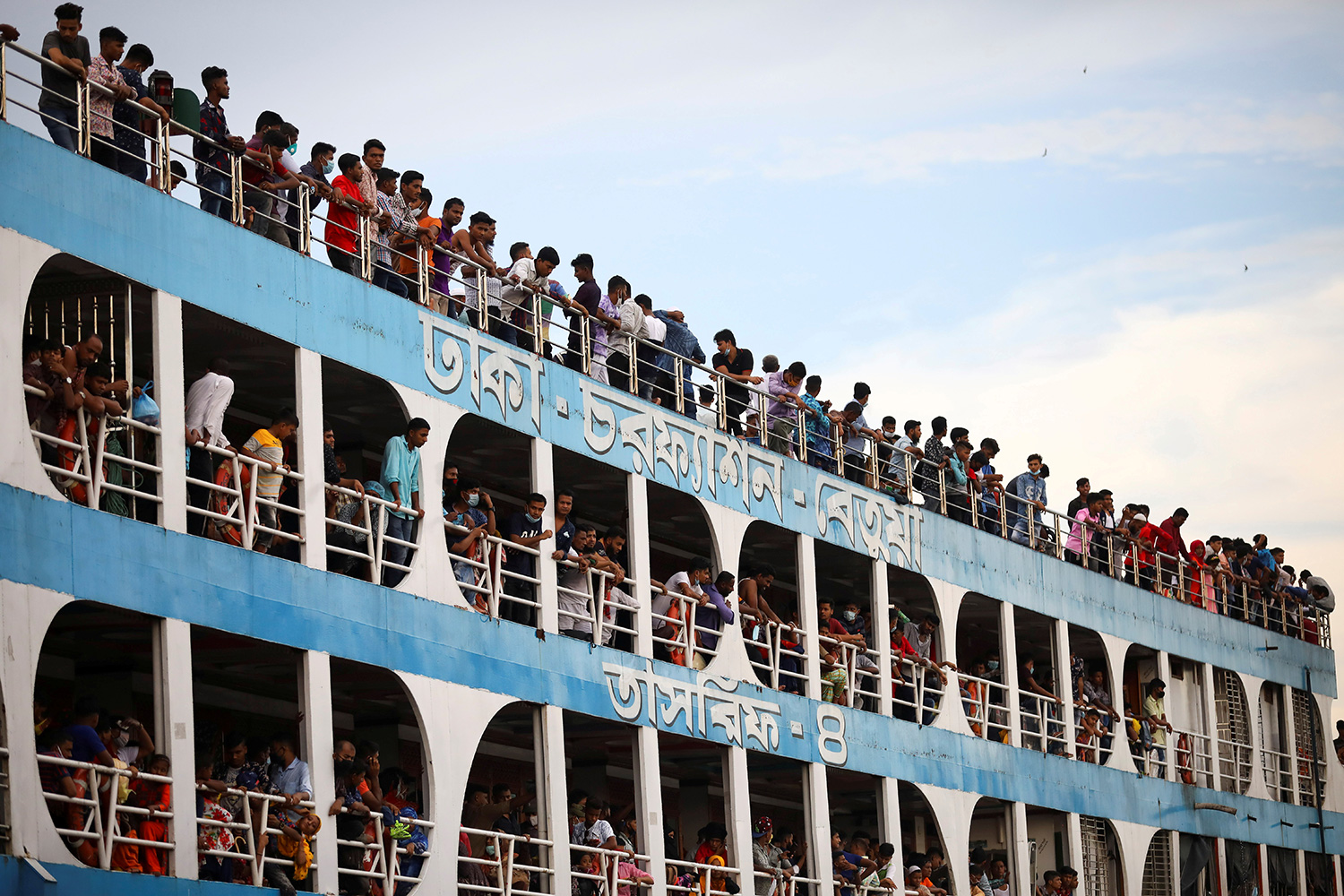 The photo shows the ferry from the side with all balconies jammed with people, most not wearing masks.