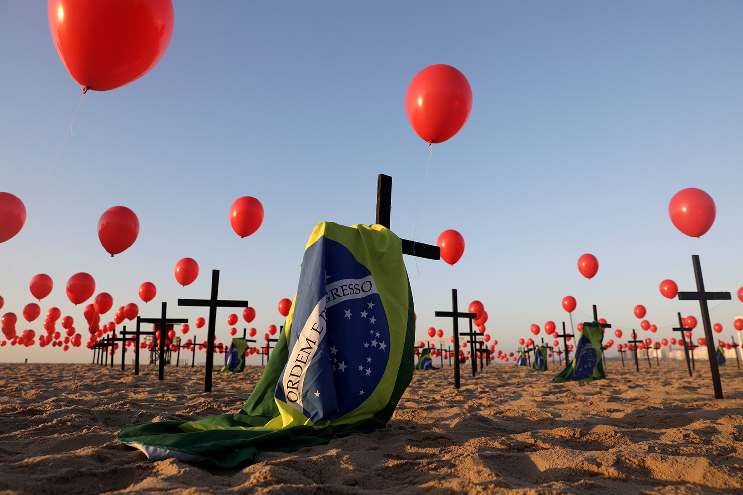 Global health security seeks to avoid installations like this one of crosses and balloons at Copacabana beach in Rio de Janeiro, Brazil, on August 8, 2020—a tribute to 100,000 victims of coronavirus. The photo shows an art installation of crosses, balloons and flag on the beach. REUTERS/Ricardo Moraes