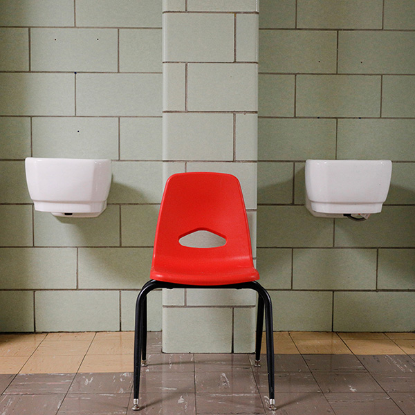 U.S. school systems are stuck between two bad choices. A classroom chair rests between two dismantled water fountains at Edmondson Westside High School in Baltimore, Maryland, on April 28, 2020. The photo shows a red chair in a beige-colorored hallway where two porticos feature white porcelain basins now dry for the pandemic. REUTERS/Tom Brenner