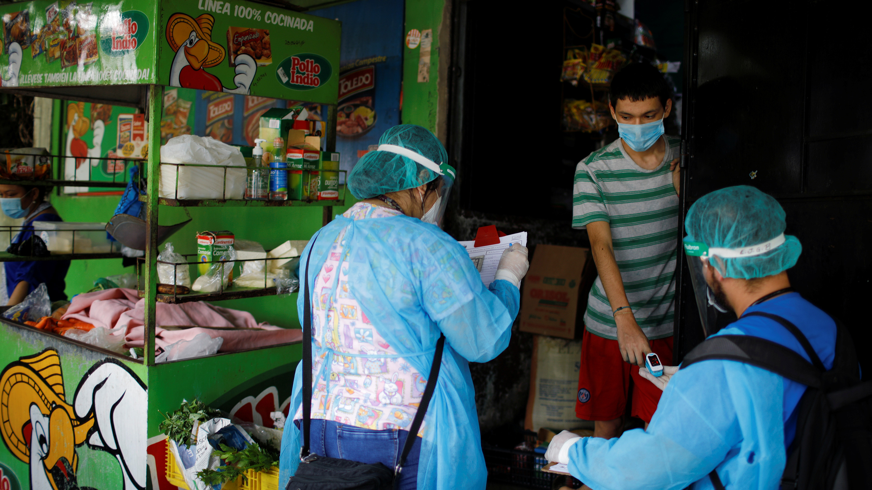 The photo shows two health workers interviewing a young person at the entrance of a small market.