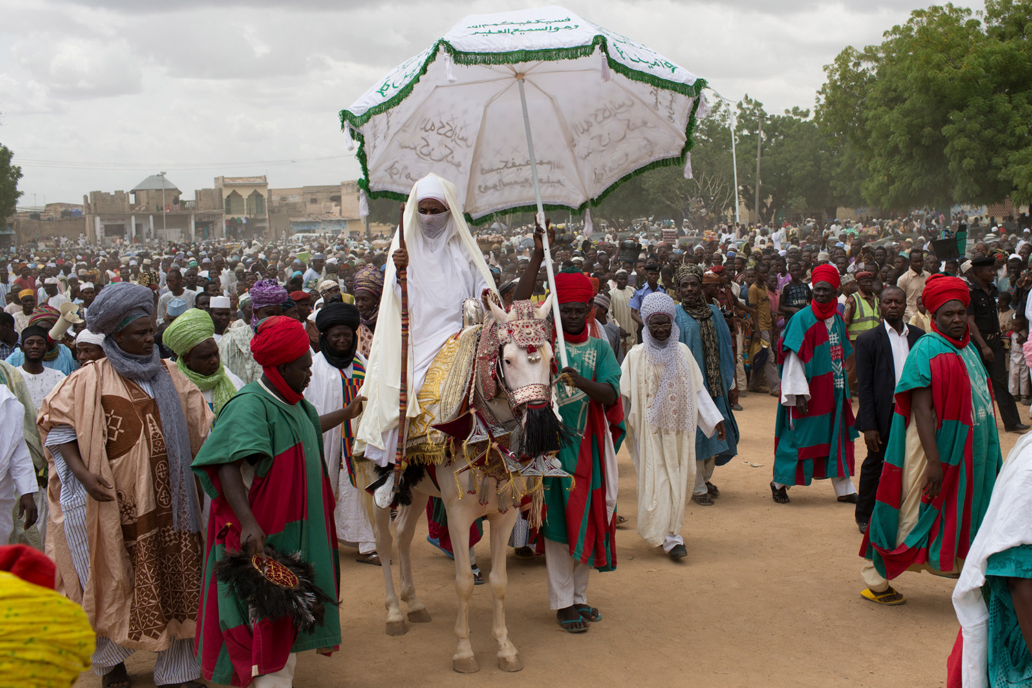 The photo shows the emir atop a horse with decorative coverings while a massive crowd surrounds him and one attendant holds an umbrella high above the emir's head.