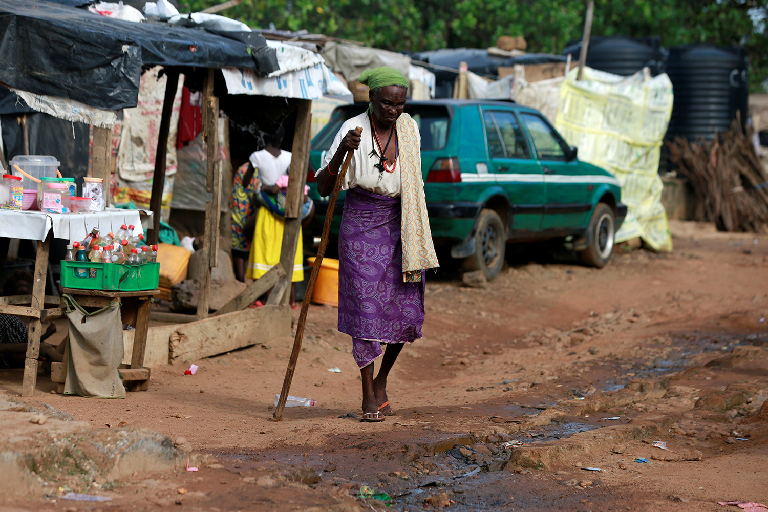 The photo shows the older woman walking along a muddy unpaved road.