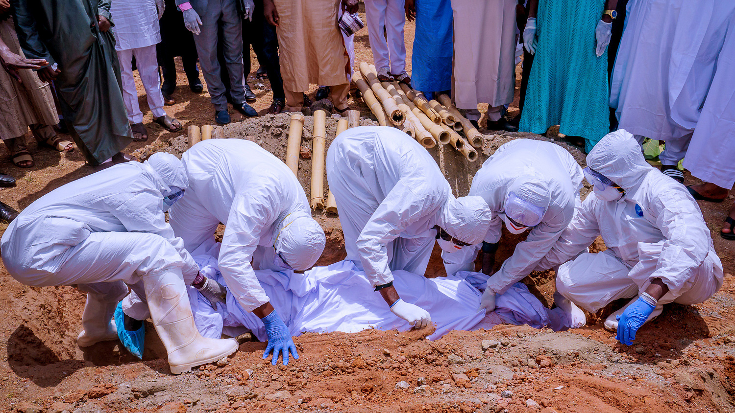 The photo shows people in protective gear lowering a body into the ground.