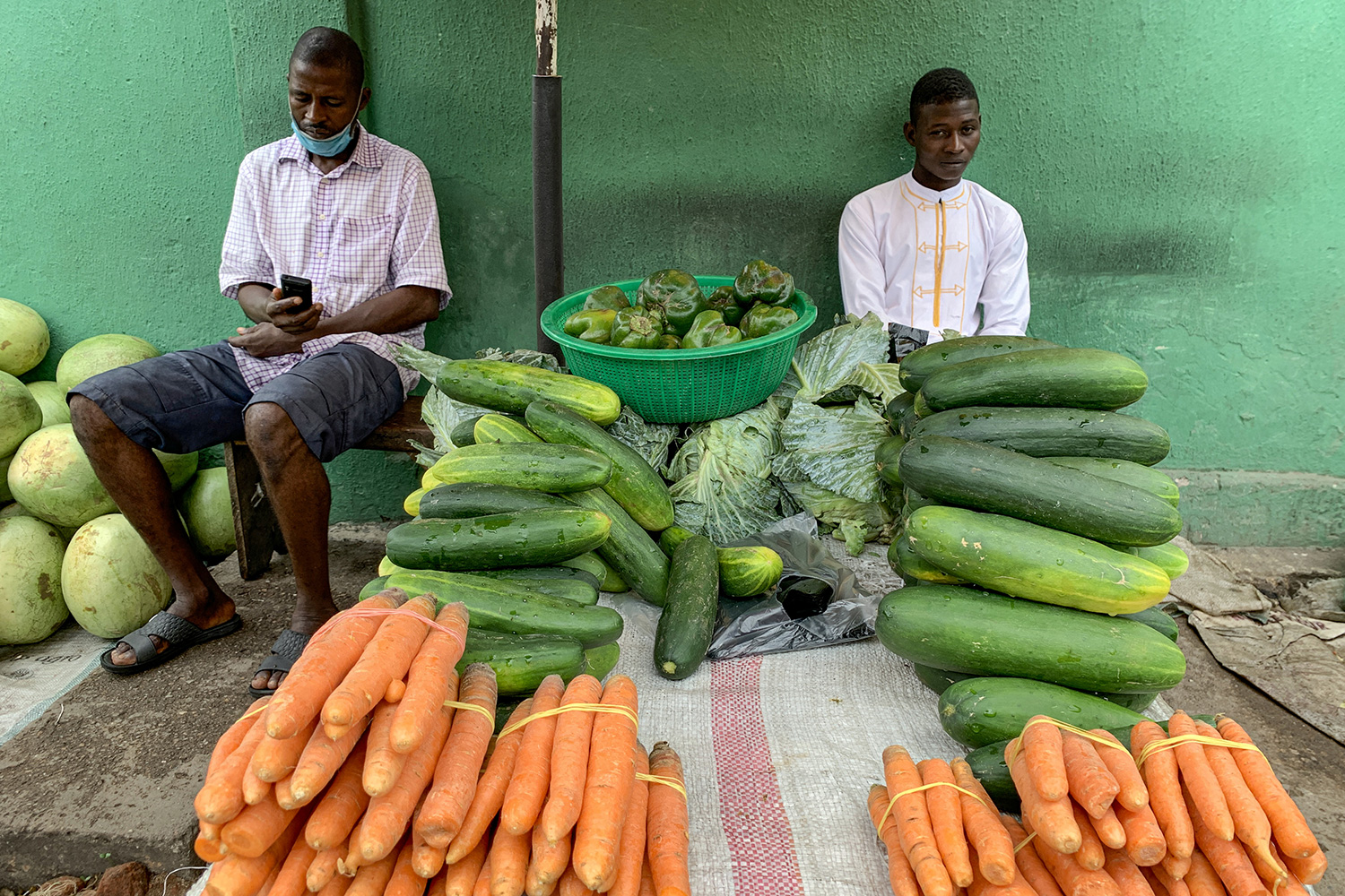 The photo shows two men amid carots, melons, zucchini and other fresh foods.