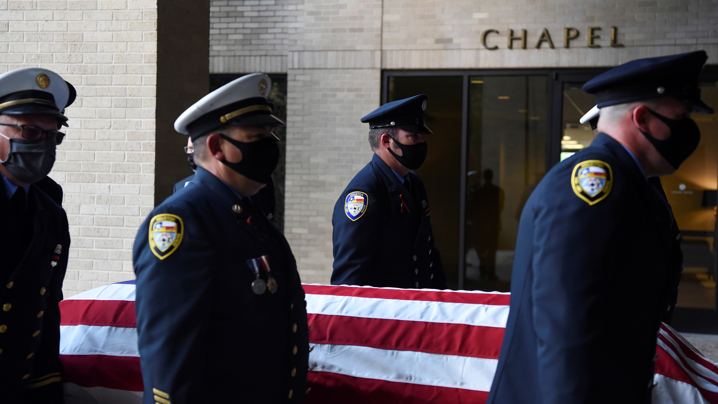 The photo shows a firefighter honor guard carrying a casket.