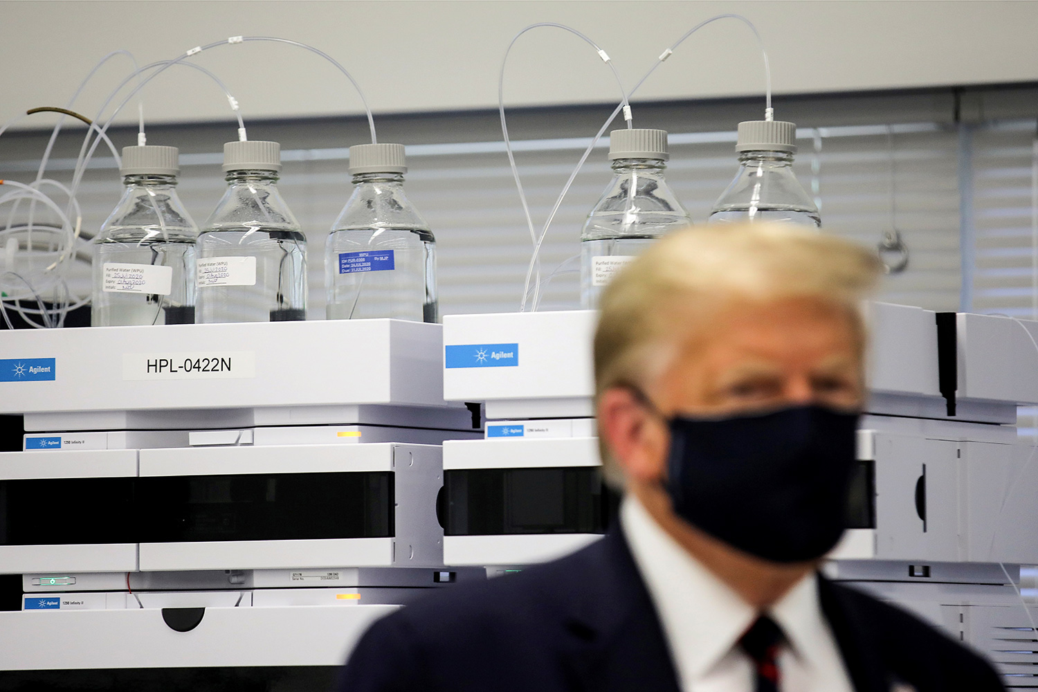 The photo shows the president wearing a mask in front of a fancy piece of equipment.