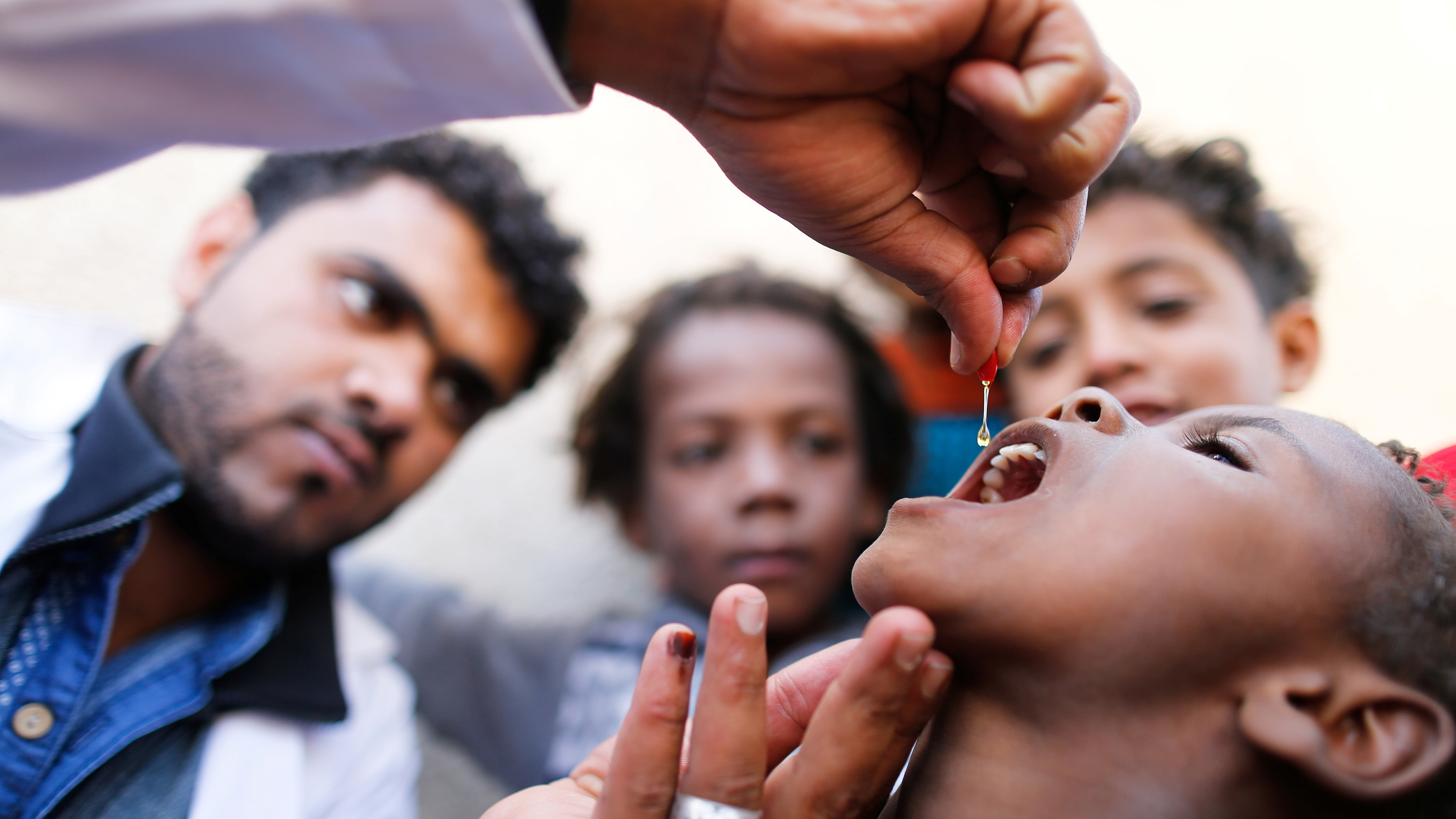 The image shows a health worker holding a dropper above a child's head. He is concentrating on the dropper, from which he is squeezing a clear liquid into the child's open mouth with family members looking on in the background.