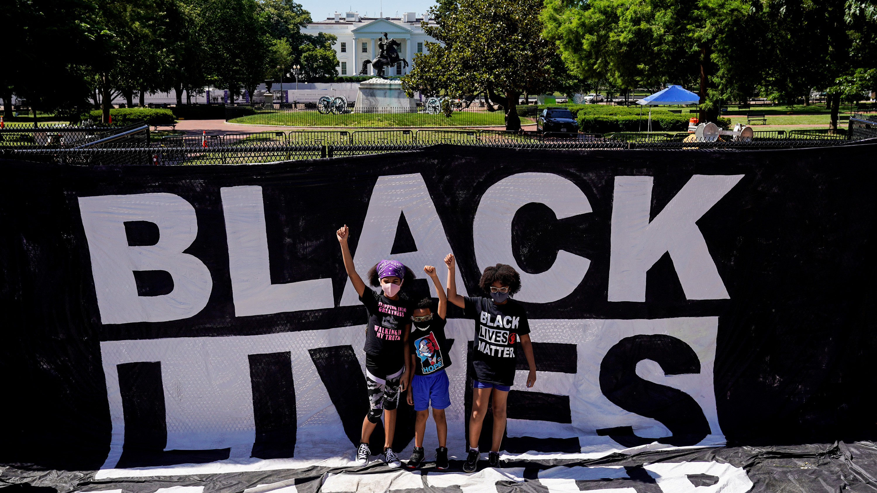The photo shows a group of small children standing amid black lives matter signs.