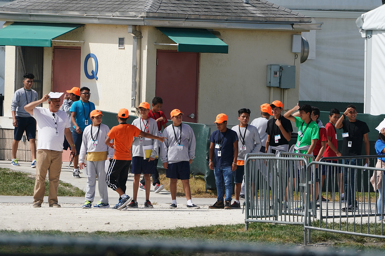 The photo shows a group of children, all with orange hats, standing in a line.