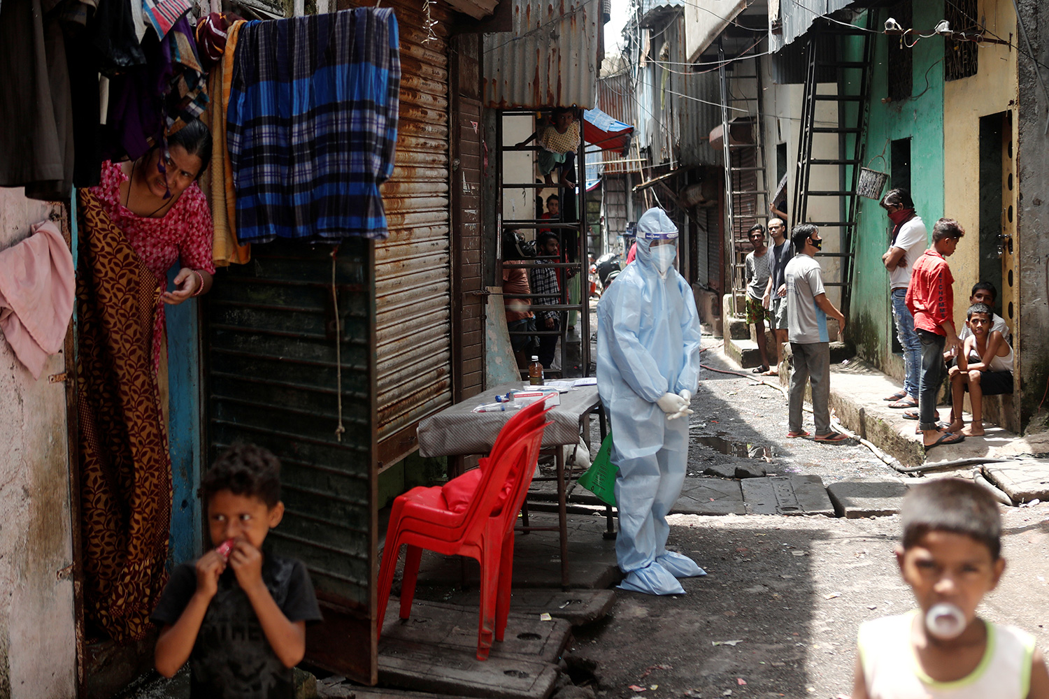 A health-care worker waits to test residents during a medical campaign for the coronavirus disease (COVID-19) at a slum area in Mumbai, India, June 30, 2020. The photo shows a worker wearing personal protective equipment standing awkwardly among residents, most of whom aren't even wearing a mask. REUTERS/Francis Mascarenhas