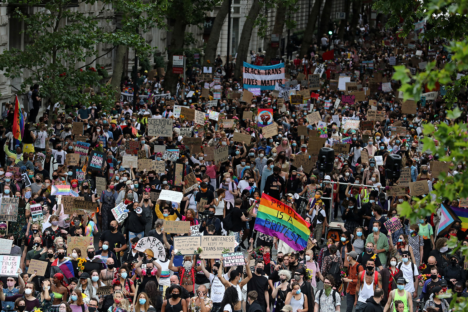 The photo shows a massive demonstration from high above with people walking through the streets of London carrying signs.