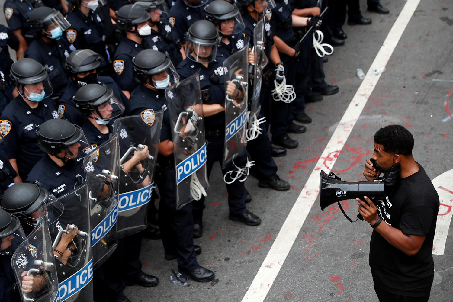 The photo shows a single protester with a bullhorn facing down a large crowd of officers.