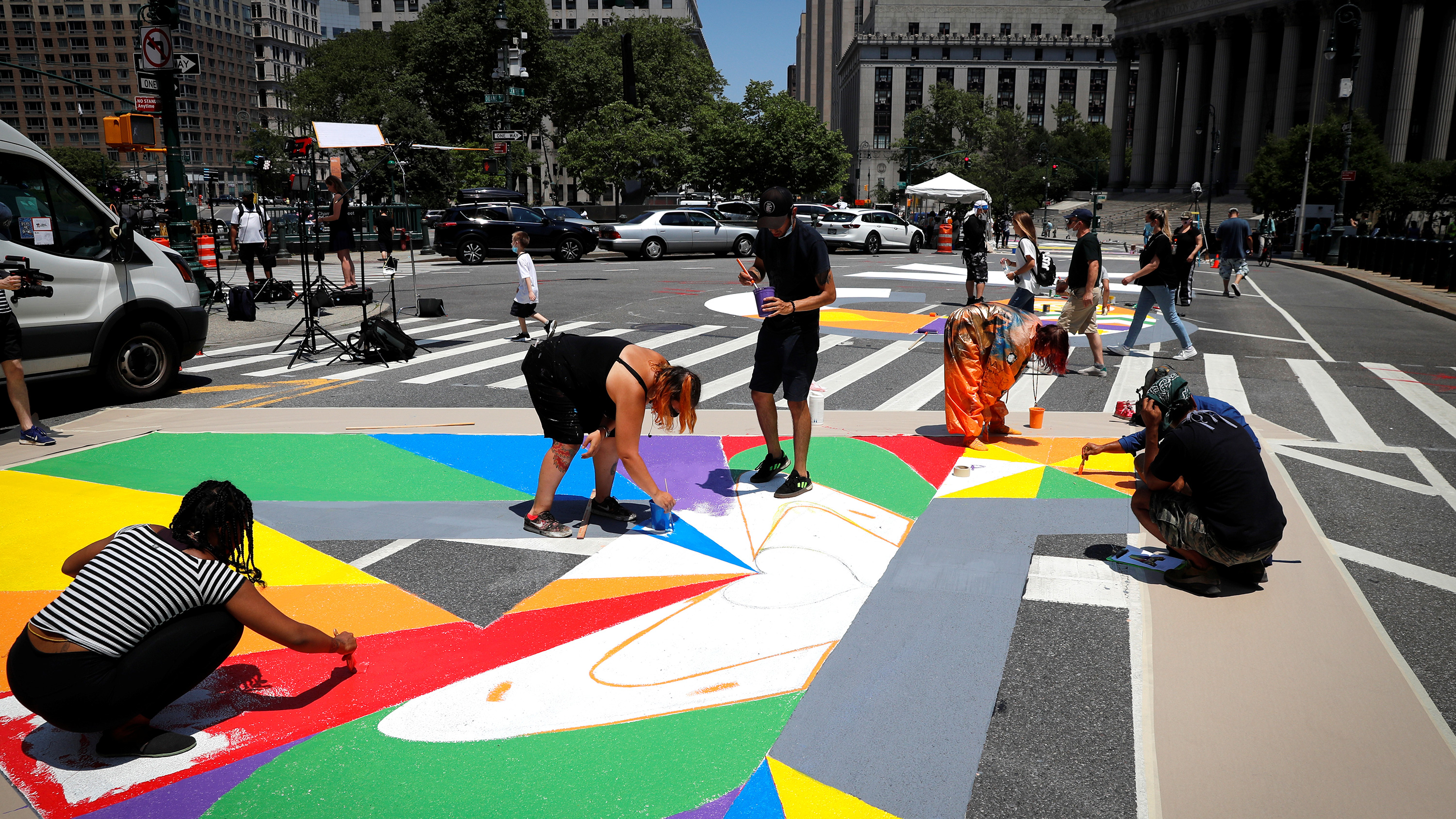 The photo shows people in the streets paining a colorful mural on the ground.