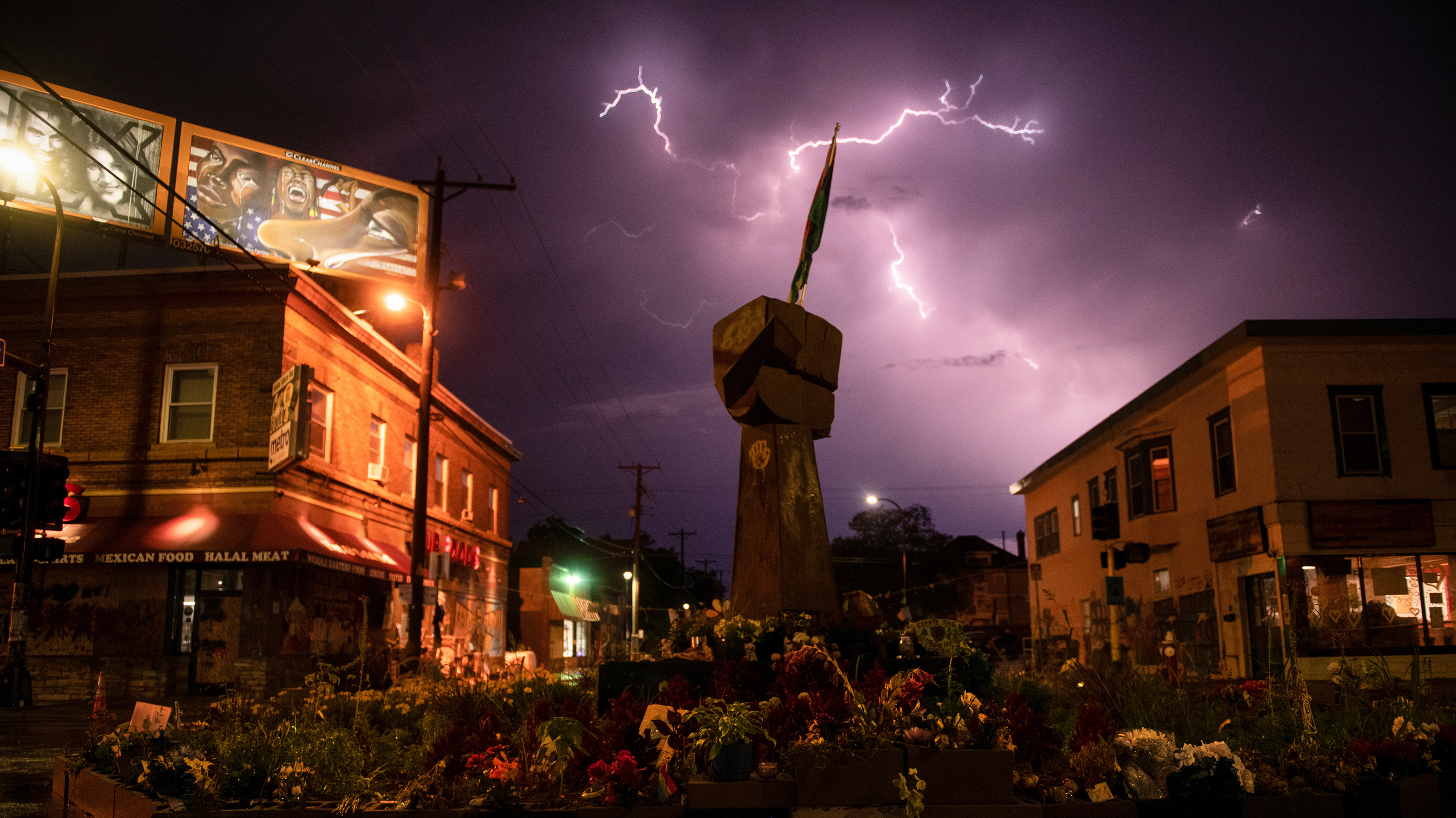 The photo shows the street where the memorial is located at night with a long-exposure photograph capturing a remarkable flash of lightning in the sky.
