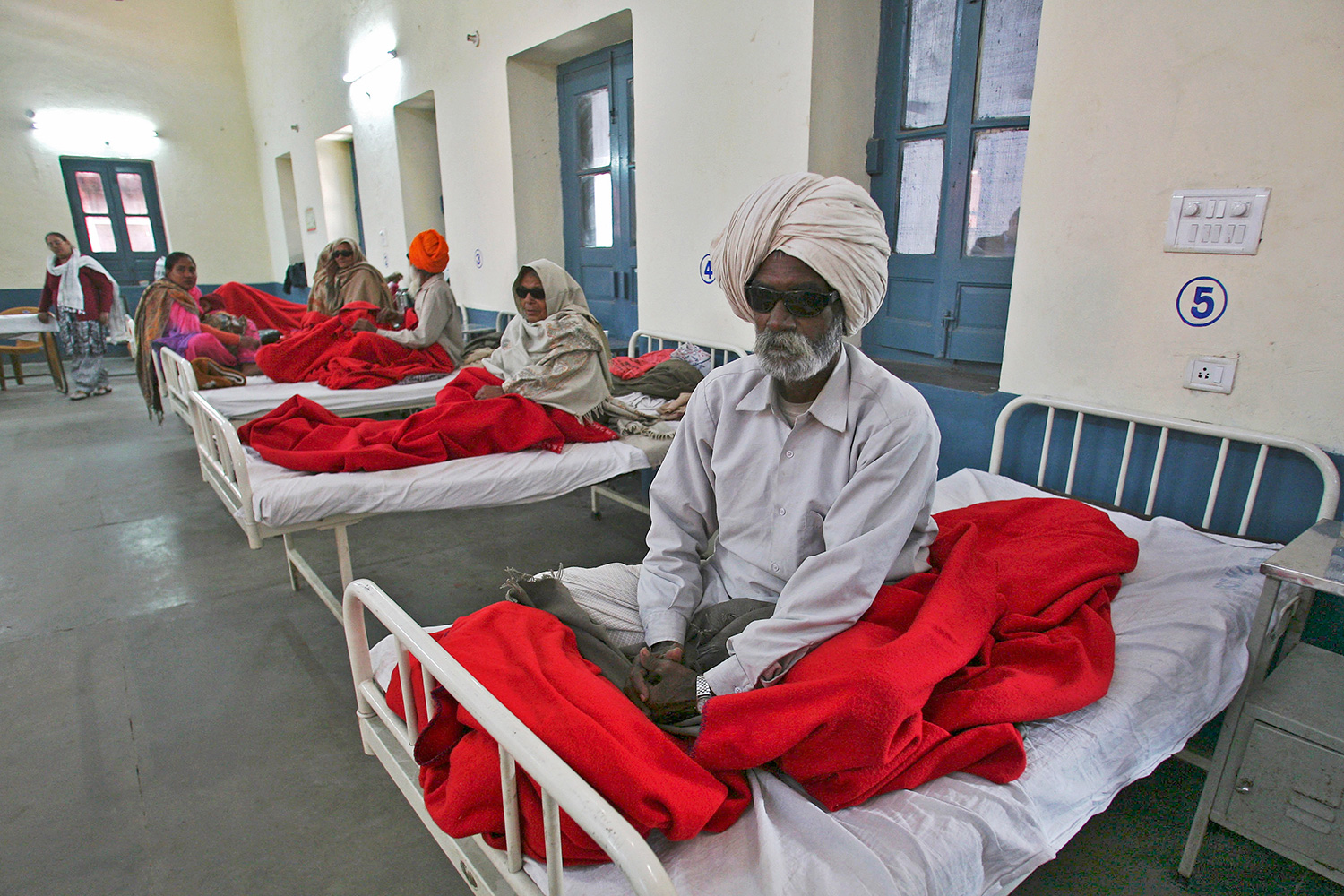 People waiting for treatment at a hospital after undergoing cataract removals from a free but shoddy eye surgery camp that caused them to lose their vision—in Amritsar, India, on December 5, 2014. The photo shows several people sitting on hospital beds. One man in the foreground is wearing dark glasses. REUTERS/Munish Sharma
