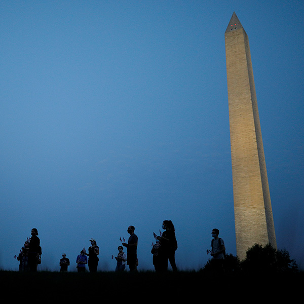 They are informally honored—but are they officially counted? Activists stand at sunrise to memorialize victims of the coronavirus, near the Washington Monument in Washington, DC on August 27, 2020. The photo shows the monument in the thin morning lite with a silhouette line of people standing in the foreground. REUTERS/Tom Brenner