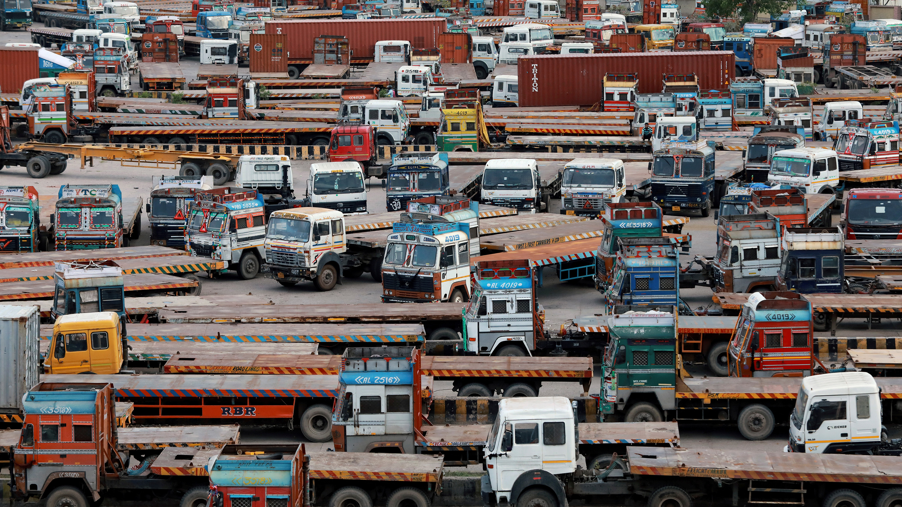 The photo shows a huge collection of large haul trucks packed together in a large parking area.