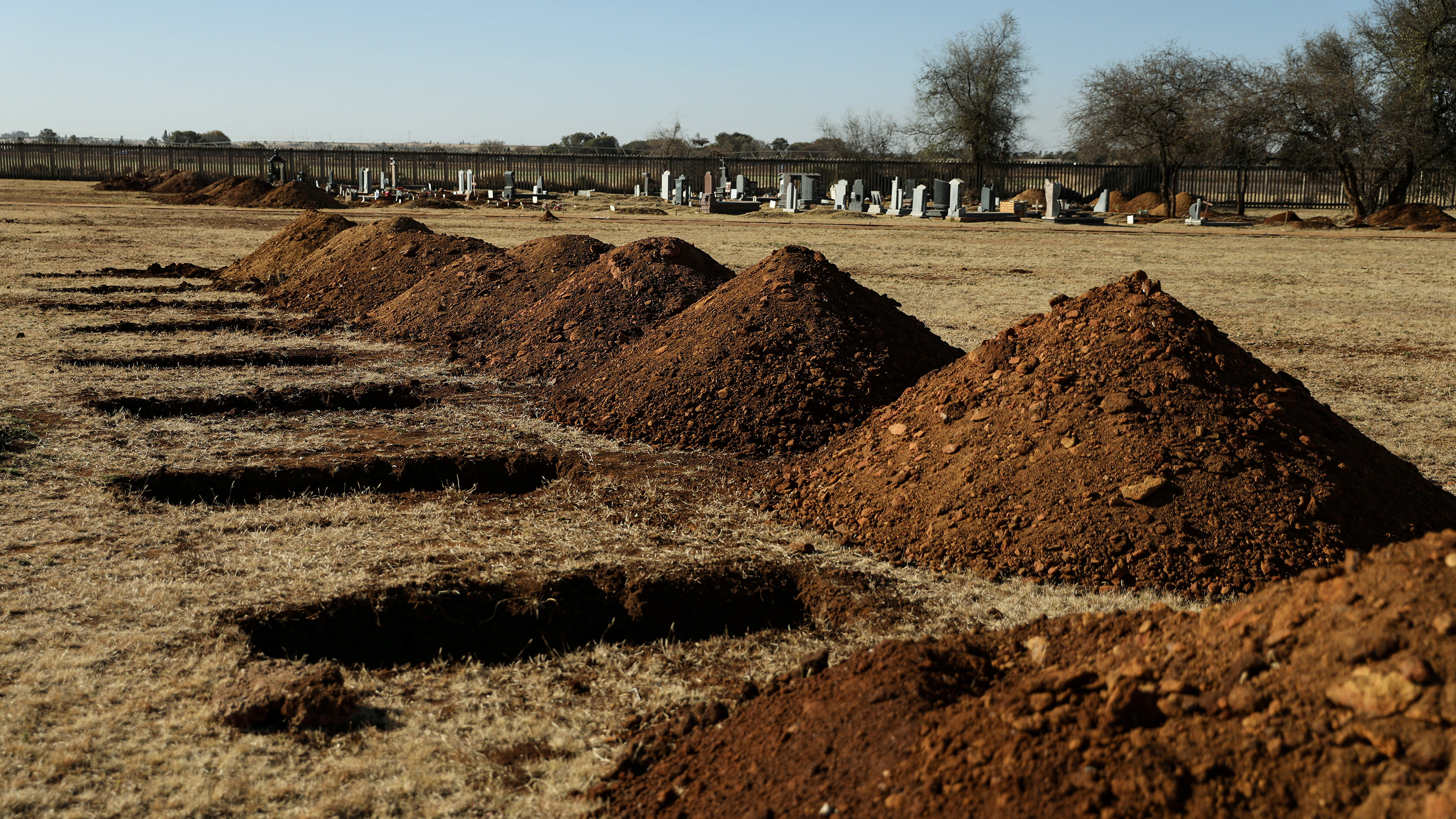 The photo shows mounds of freshly turned dirt next to open graves.