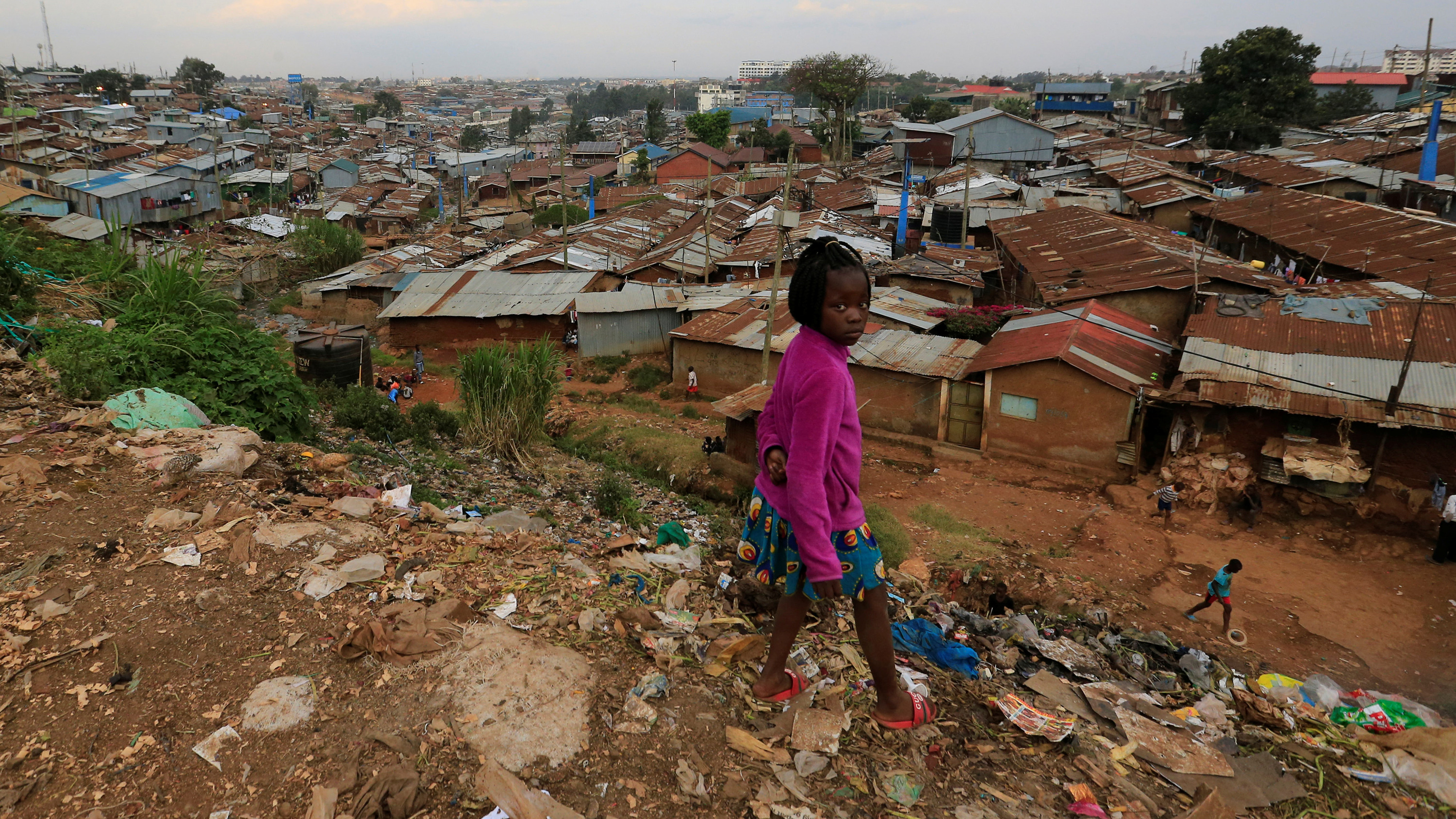 The photo shows a girl standing atop a hill littered with trash overlooking a residential area of poor houses with rusty metal roofing.
