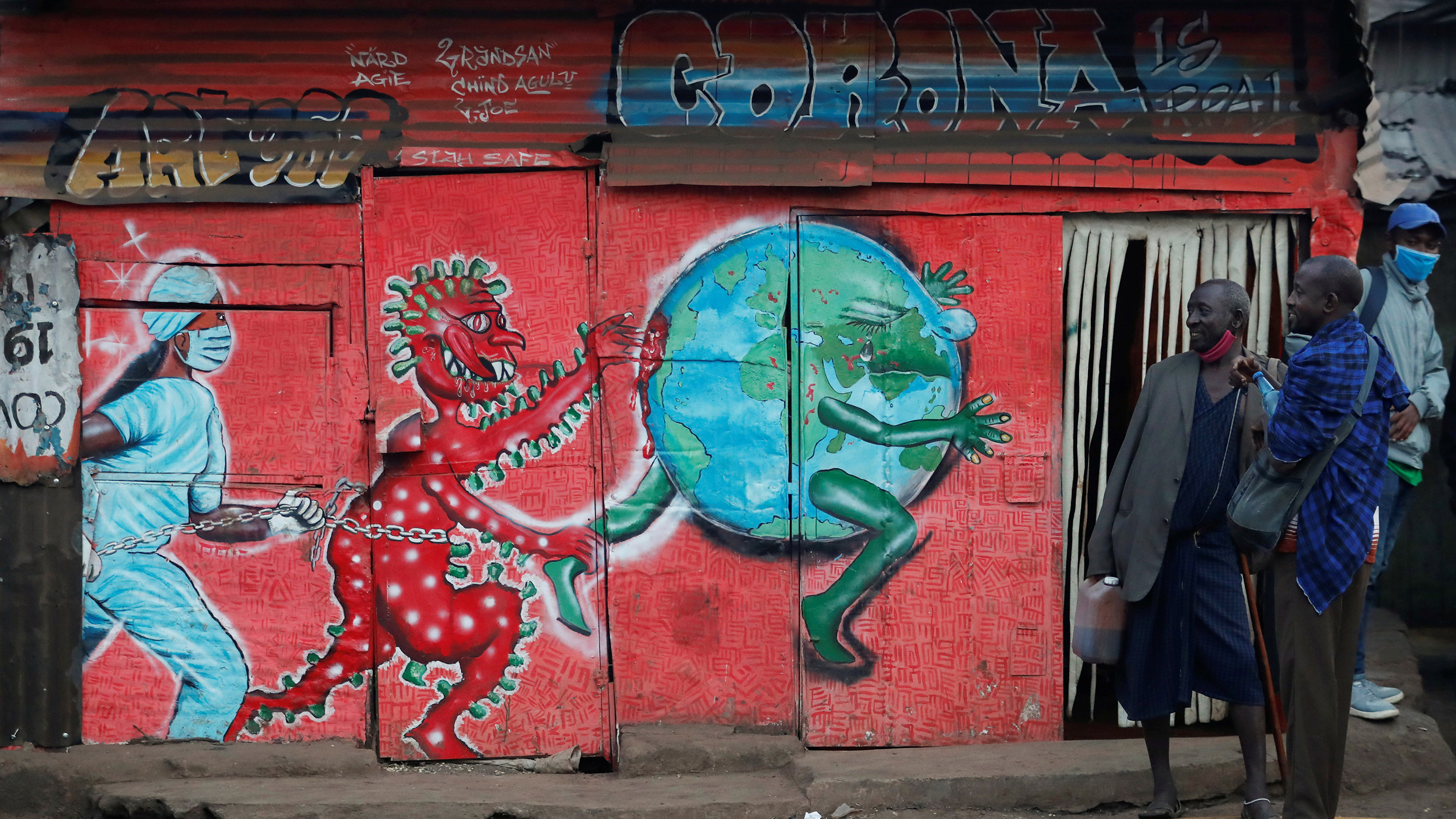 The photo shows a few people milling ablut the entrance of a building on the side of which is painted a mural with a red figure representing the personification of coronavirus chasing a globe while a nurse follows behind in hot pursuit.