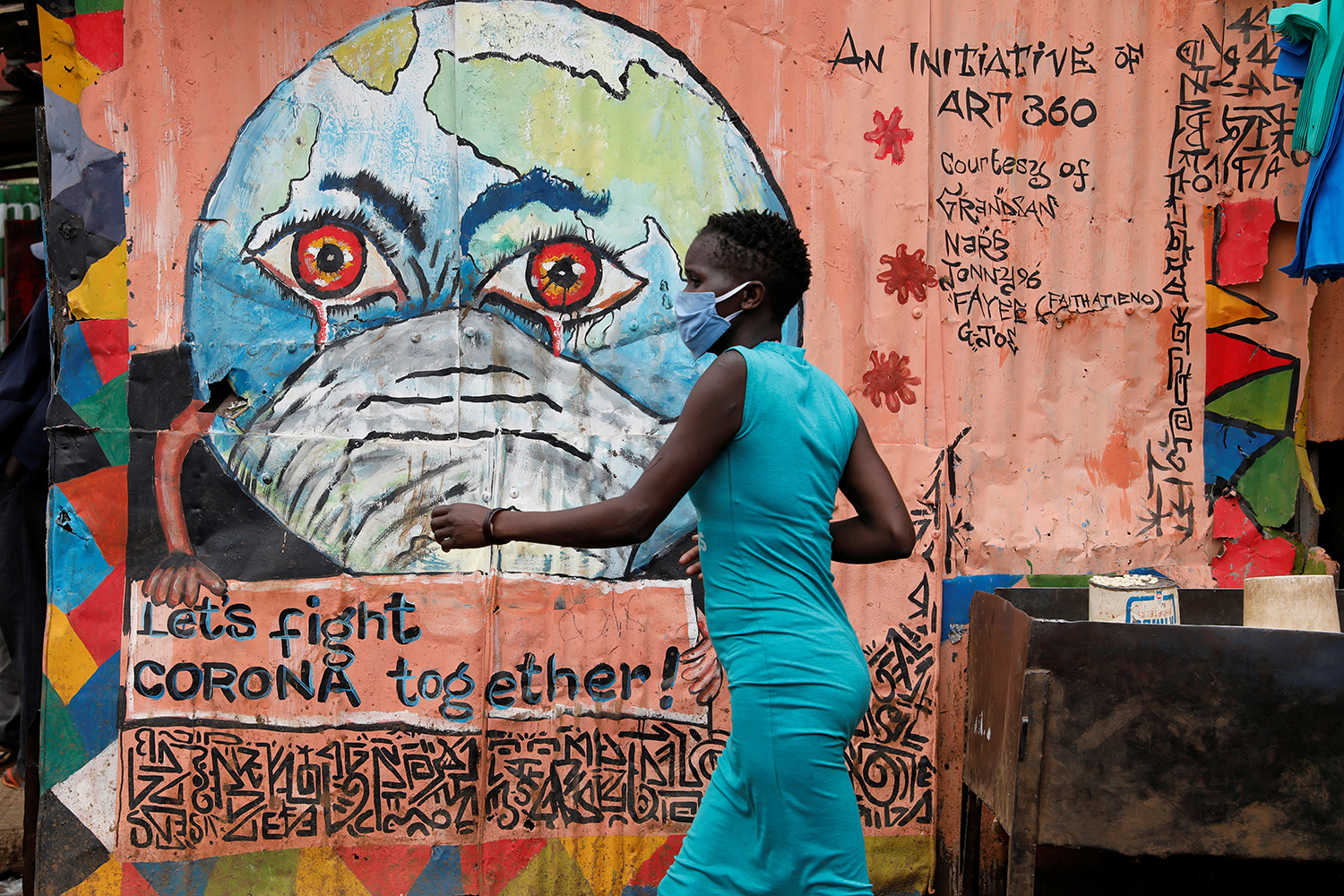 A woman walks past a graffiti promoting the fight against the spread of the coronavirus disease (COVID-19) in the Kibera slums of Nairobi, Kenya, on May 22, 2020. This is a striking photo of a woman in a blue dress wearing a facemask walking past a peach-colored wall with a graffiti of the Earth, also wearing a facemask, with bloodshot eyes and crying. REUTERS/Baz Ratner