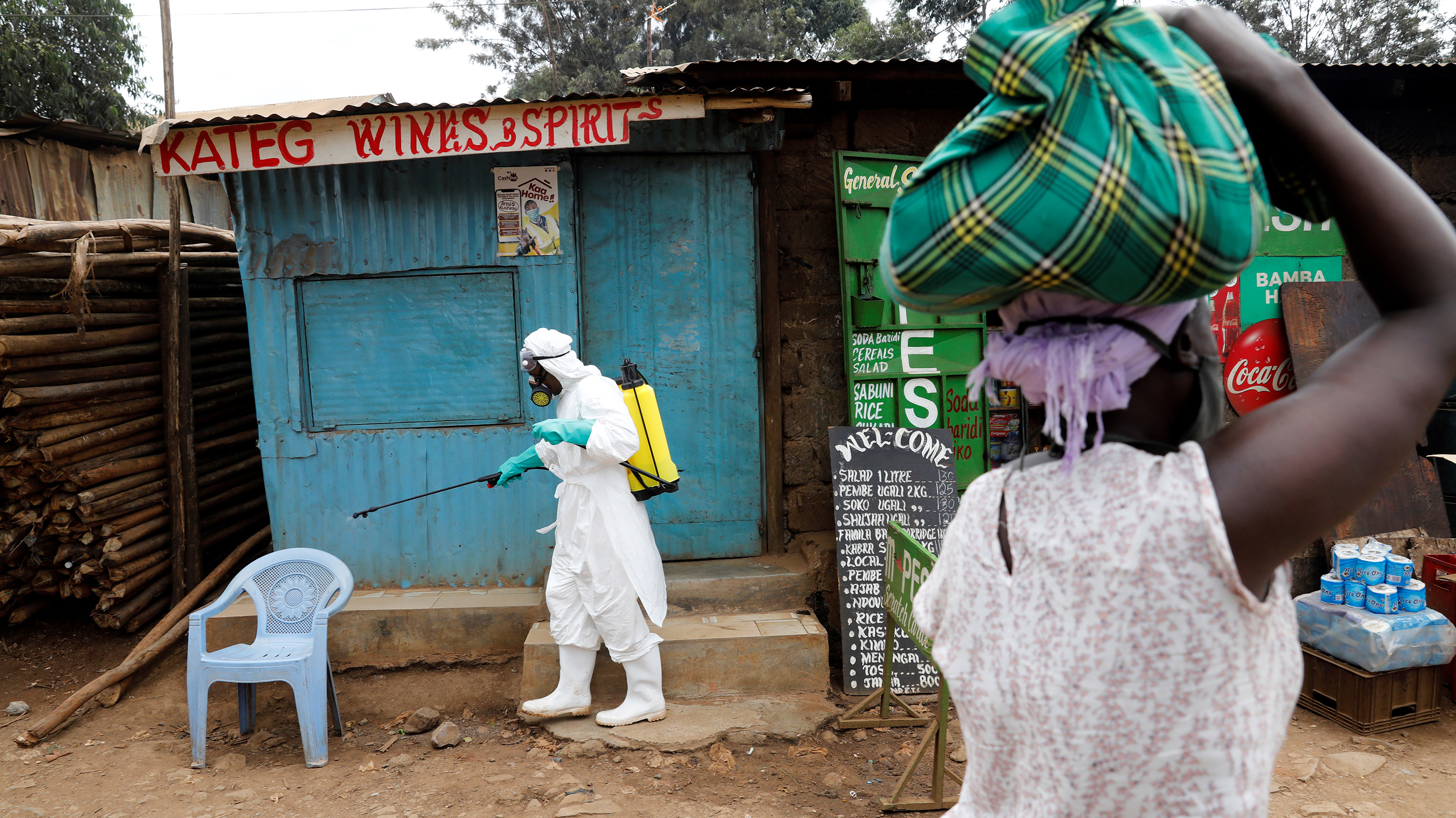 The photo shows a health worker in protective gear spraying from a bottle while a woman in the foreground looks on.