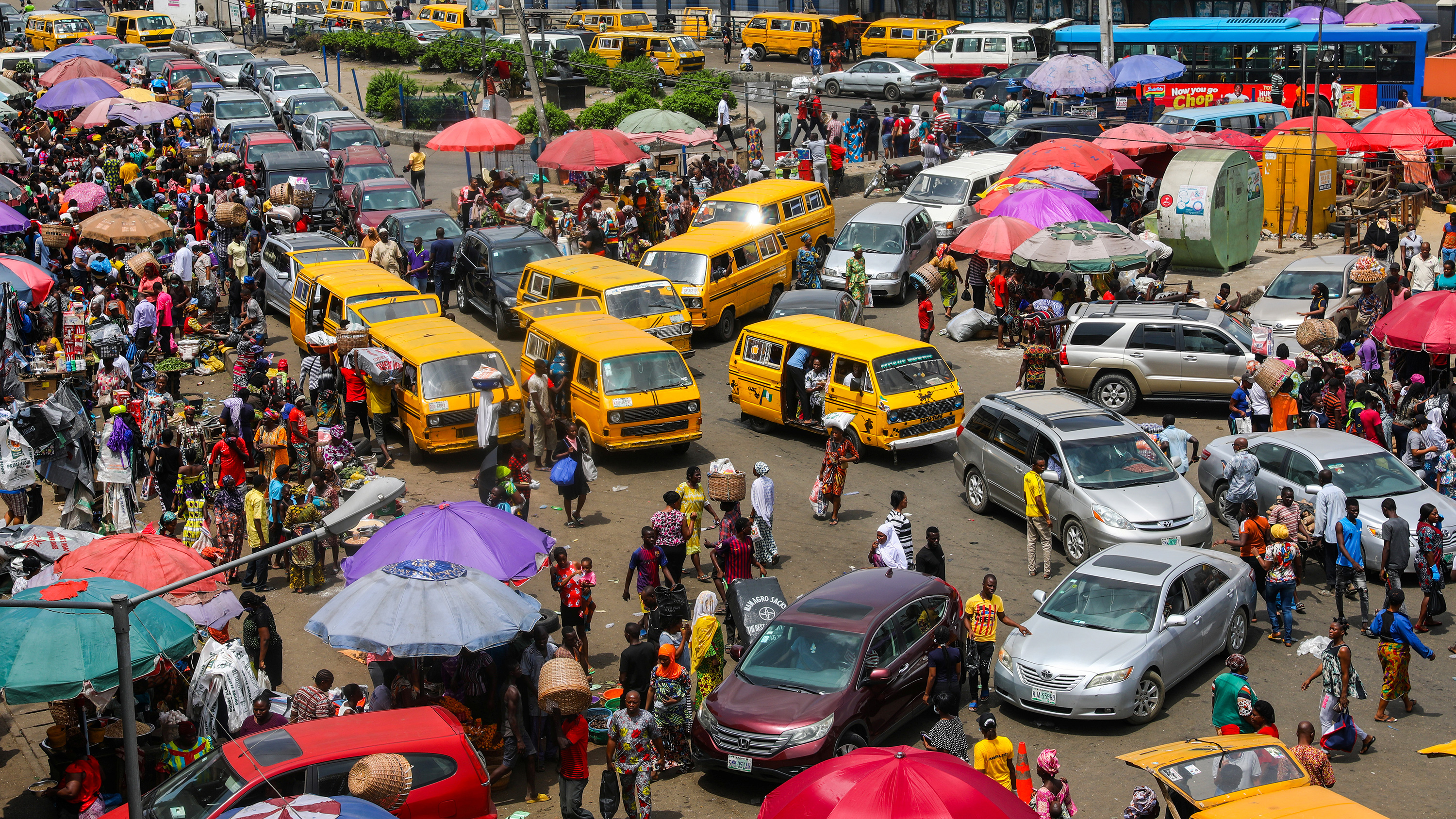 The photo shows a bustling market crowded with people and cars.