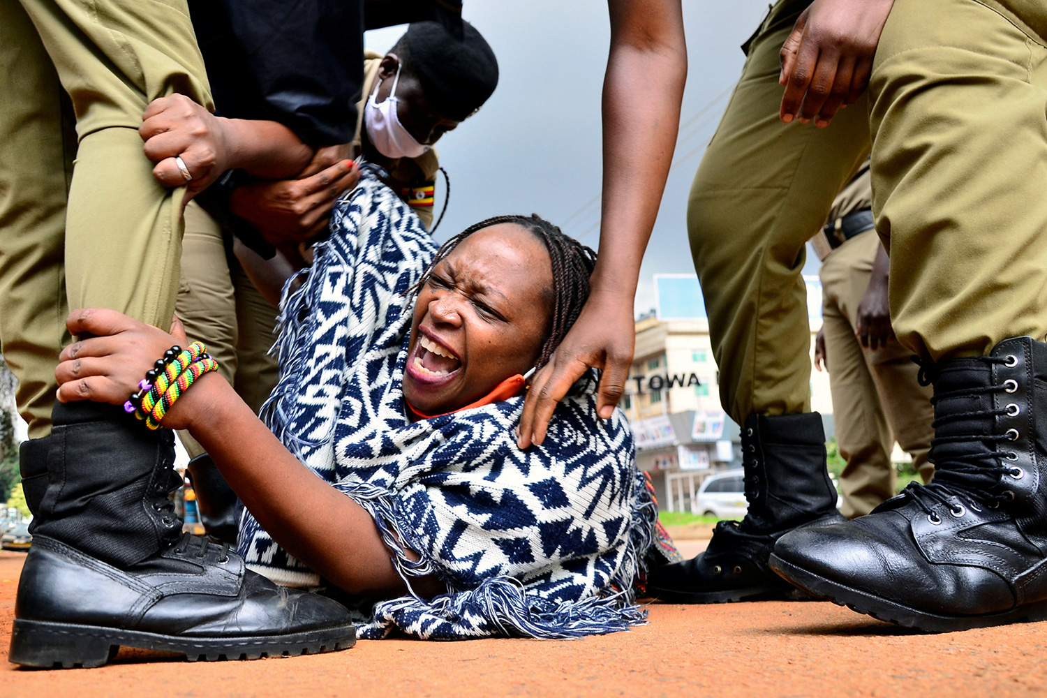 The photo shows the professor on the ground shouting as she clings to the leg of one uniformed officer while another reaches to grab her shoulder.