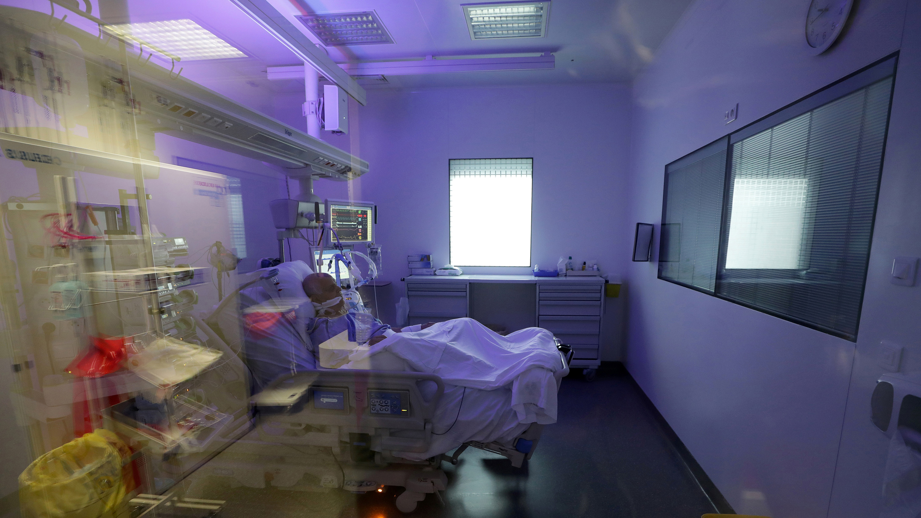 The photo shows a hospital room with a patient in a bed in the middle. The room is bathed in purple light.