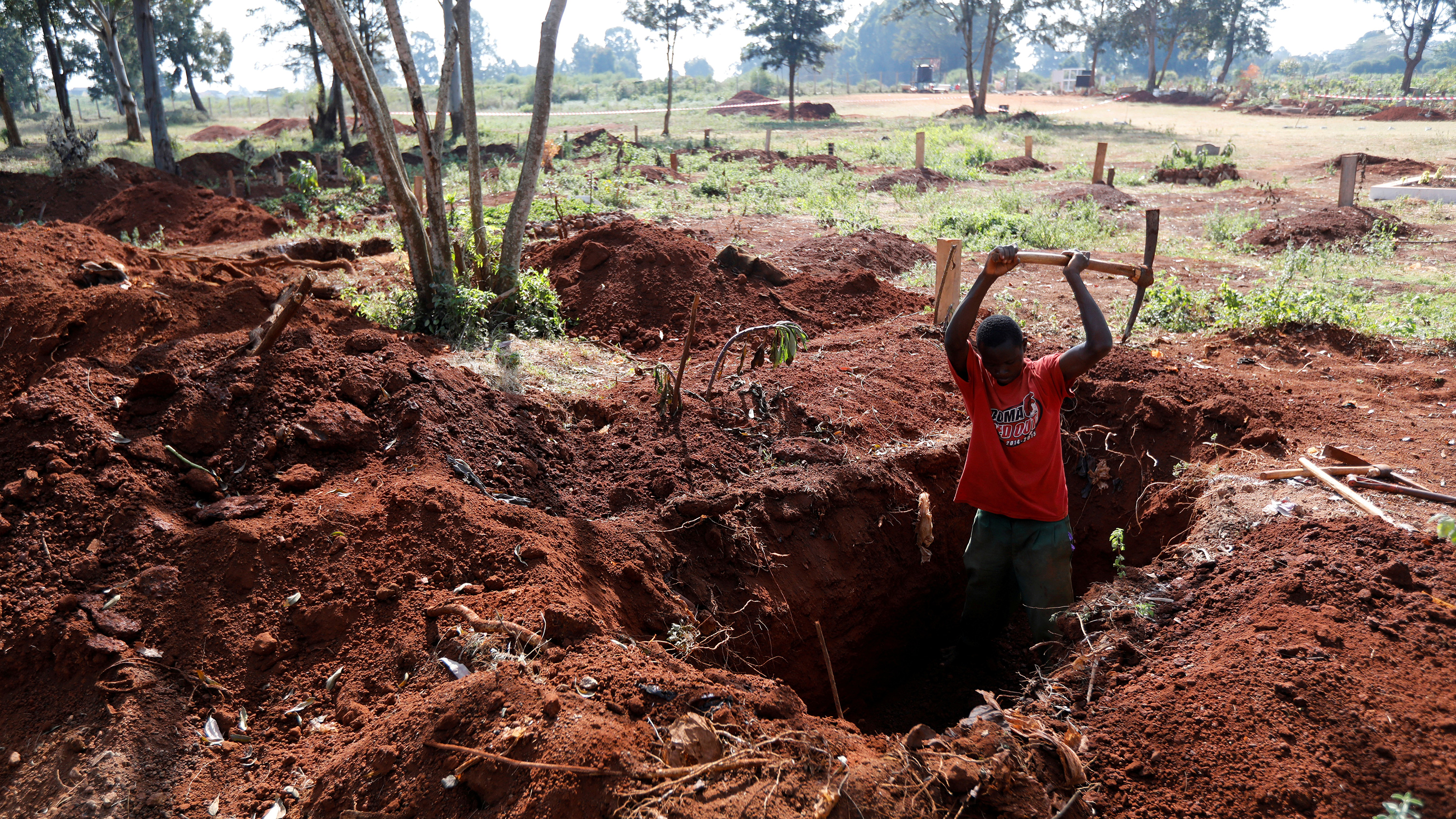 The photo shows a worker chest deep in an oblong hole actively swinging his pick into the red earth with lots of other freshly dug graves visible in the background.