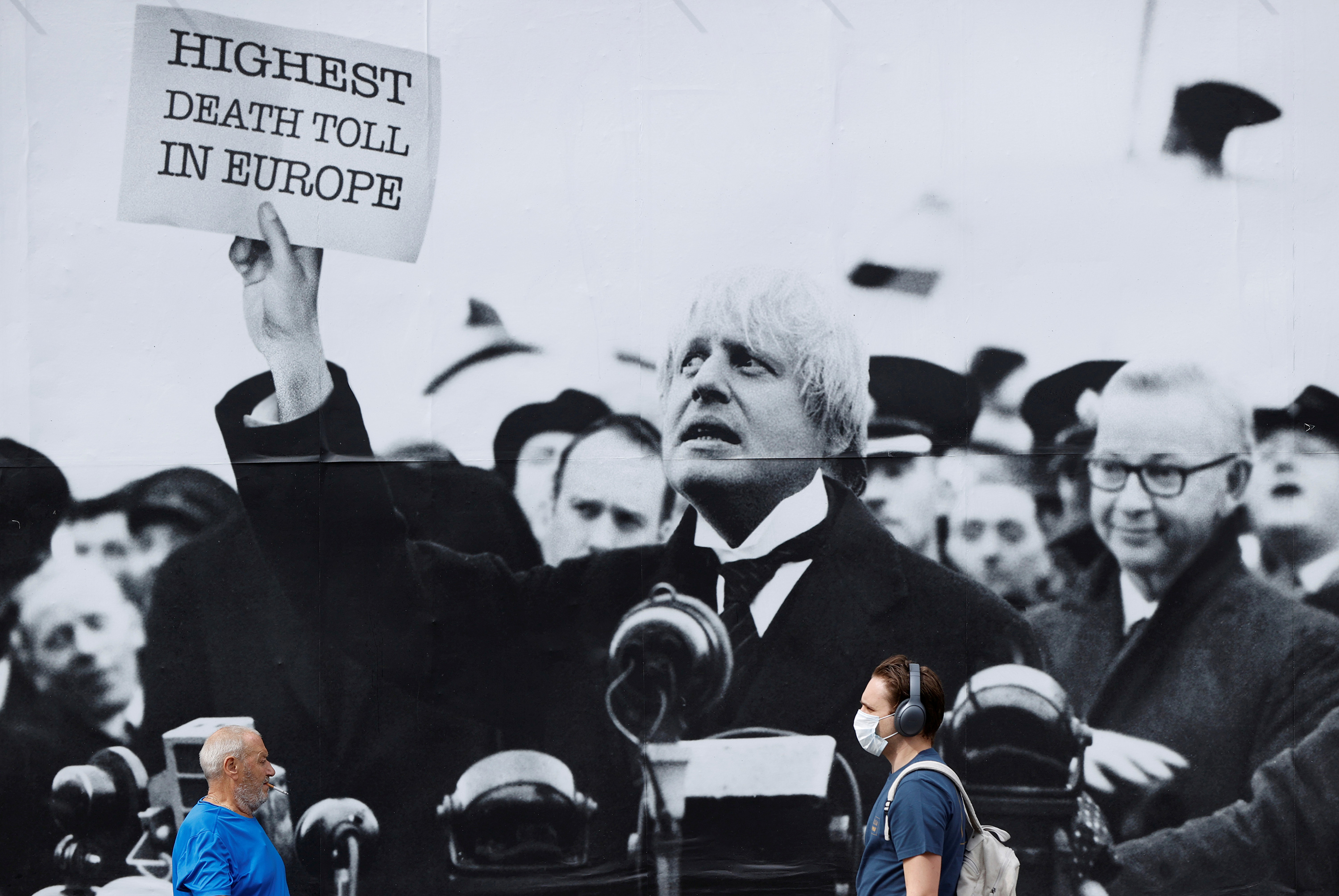 "The photo shows a few people walking by a huge sign with a black and white picture of the PM holding up a placard that reads, ""Highest Death Toll in Europe."""