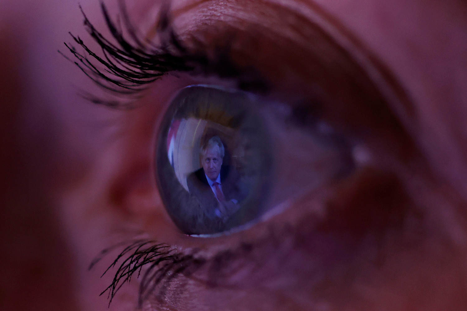 Britain's Prime Minister Boris Johnson is reflected in a woman's eye as she watches his address to the nation following the outbreak of coronavirus in Manchester, England, on September 22, 2020. The photo shows a macro lens image of an eye with the image of the PM reflected in it. REUTERS/Phil Noble