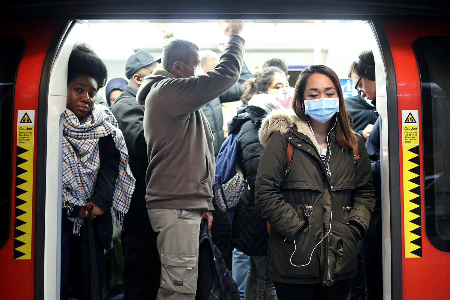 The photo shows the open door of the subway train crowded with commuters, some of whom are not wearing masks.