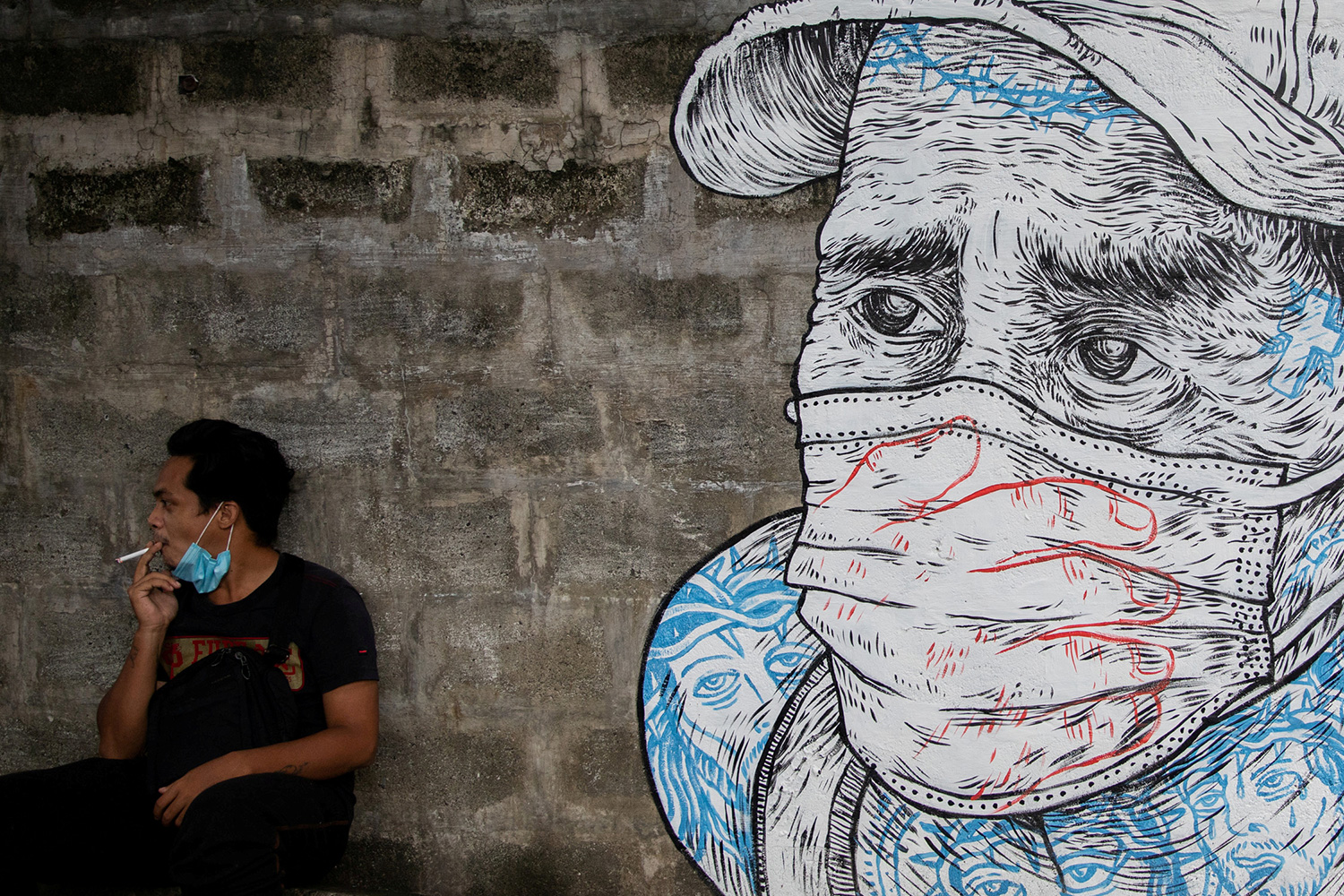 A man smokes a cigarette next to a mural of a man wearing a protective mask amid the coronavirus disease (COVID-19) outbreak in Quezon City, Metro Manila, Philippines, July 30, 2020. The photo shows a man wearing a mask pulled down around his chin smoking. Next to him is a mural of a worried-looking man in a mask. REUTERS/Eloisa Lopez