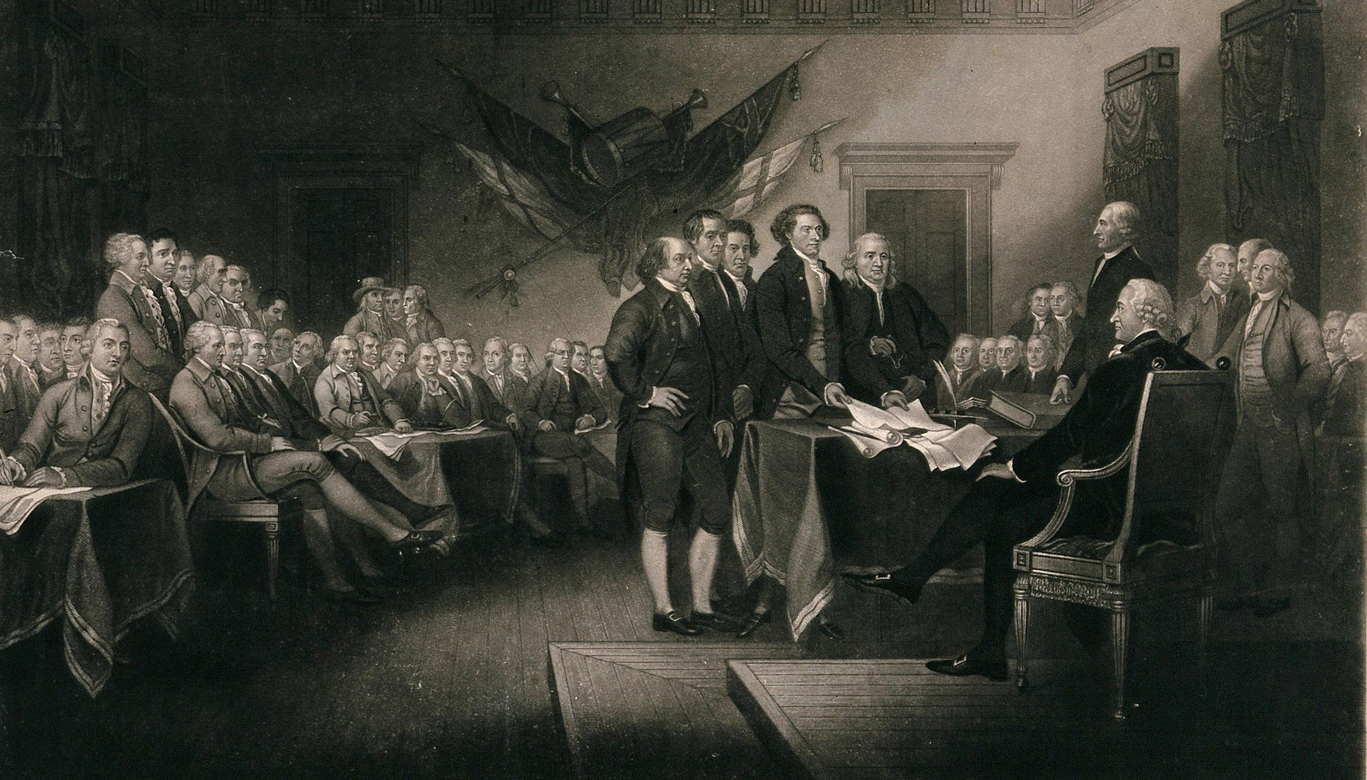 The image is taken from a famous depiction by after J. Trumbull and shows early colonial leaders gathered around the document in Philadelphia.