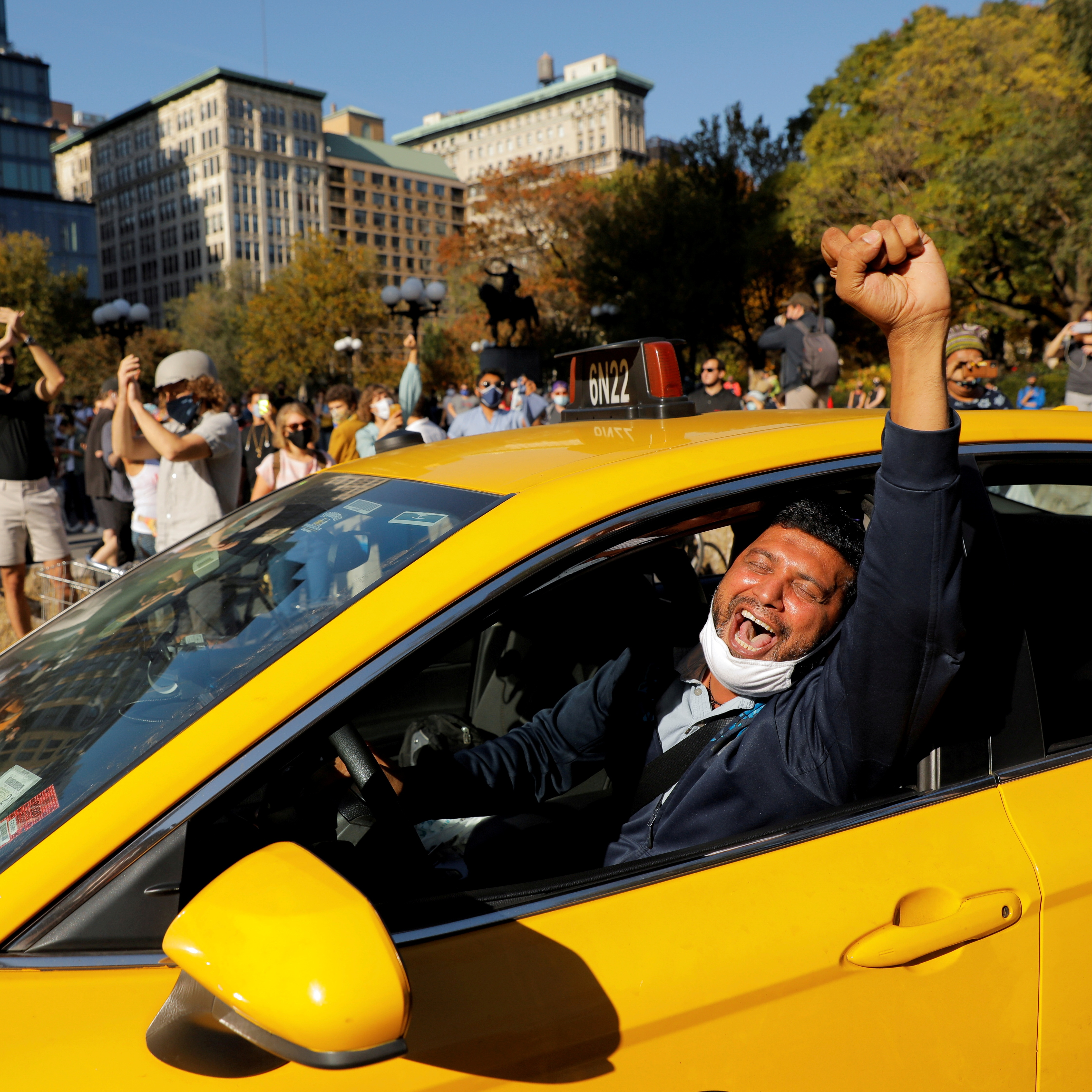 A cab driver raises his fist as people celebrate media announcements that Democratic U.S. presidential nominee Joe Biden has won the 2020 U.S. presidential election on Union Square in the Manhattan borough of New York City, U.S.